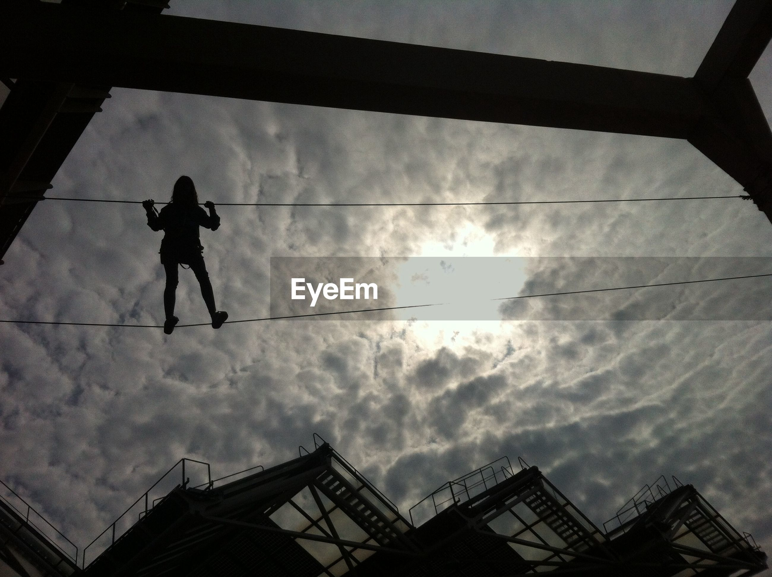 low angle view, built structure, sky, architecture, silhouette, cloud - sky, building exterior, sculpture, cloudy, cloud, human representation, statue, men, day, art and craft, outdoors, power line, cable