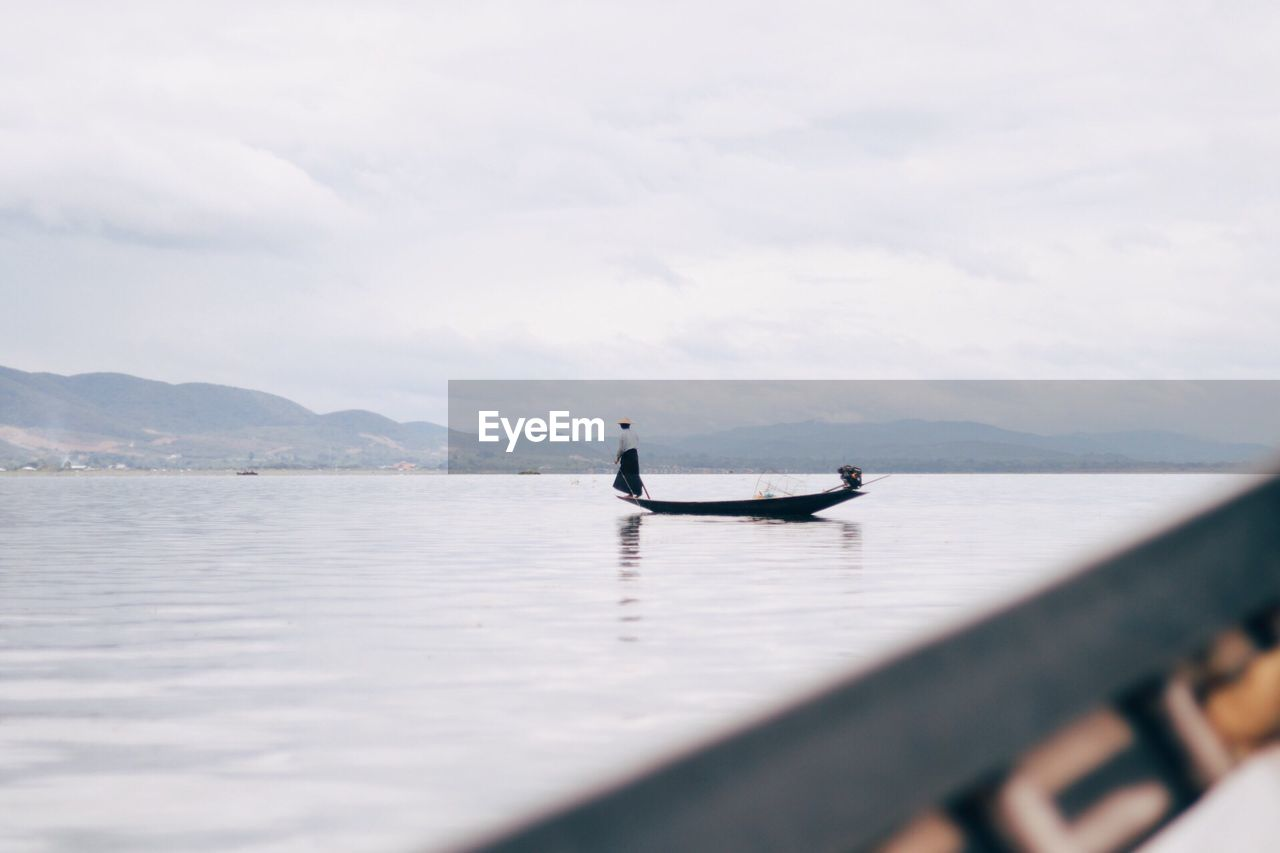 Mid distance view of woman standing in boat on sea against cloudy sky