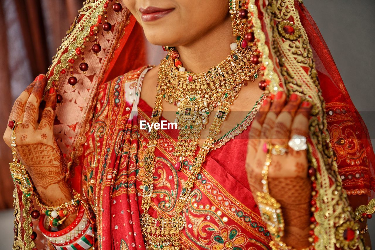 traditional clothing, one person, clothing, adult, women, life events, wedding, newlywed, bride, front view, focus on foreground, lifestyles, real people, jewelry, sari, indoors, event, beautiful woman, wedding ceremony