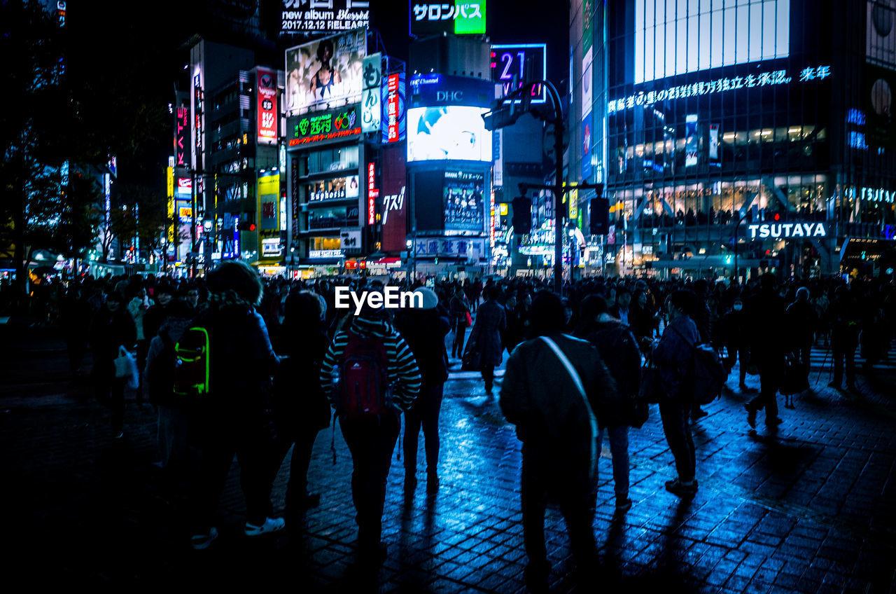 Crowd Walking On Illuminated City Street At Night