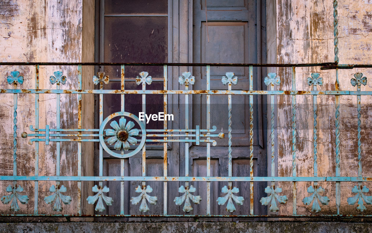 architecture, building exterior, metal, built structure, no people, wood - material, window, building, entrance, day, old, house, door, rusty, wheel, closed, protection, gate, safety, wall - building feature, outdoors, iron - metal, wrought iron