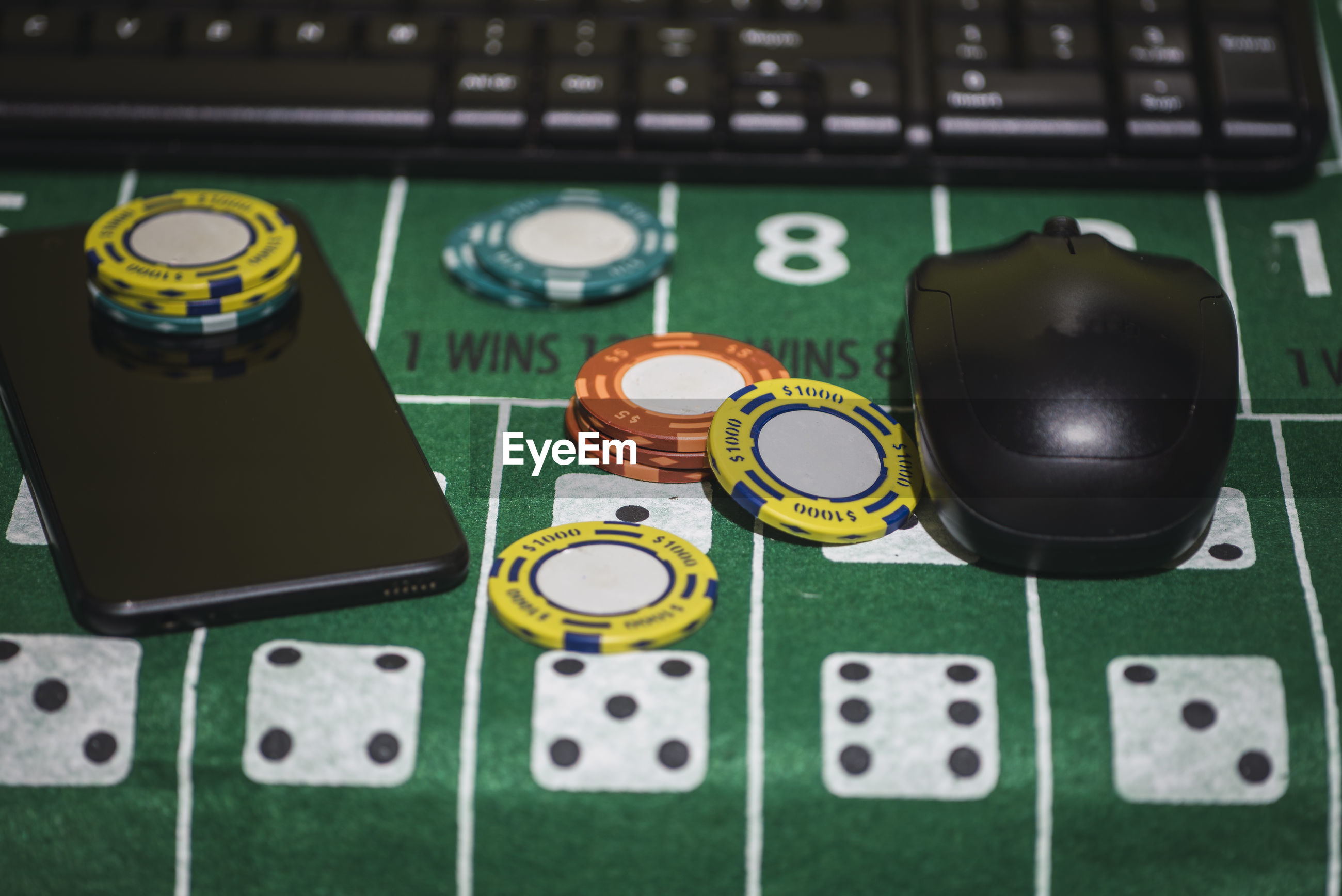 Close-up of gambling chips with computer equipment and smart phone on table