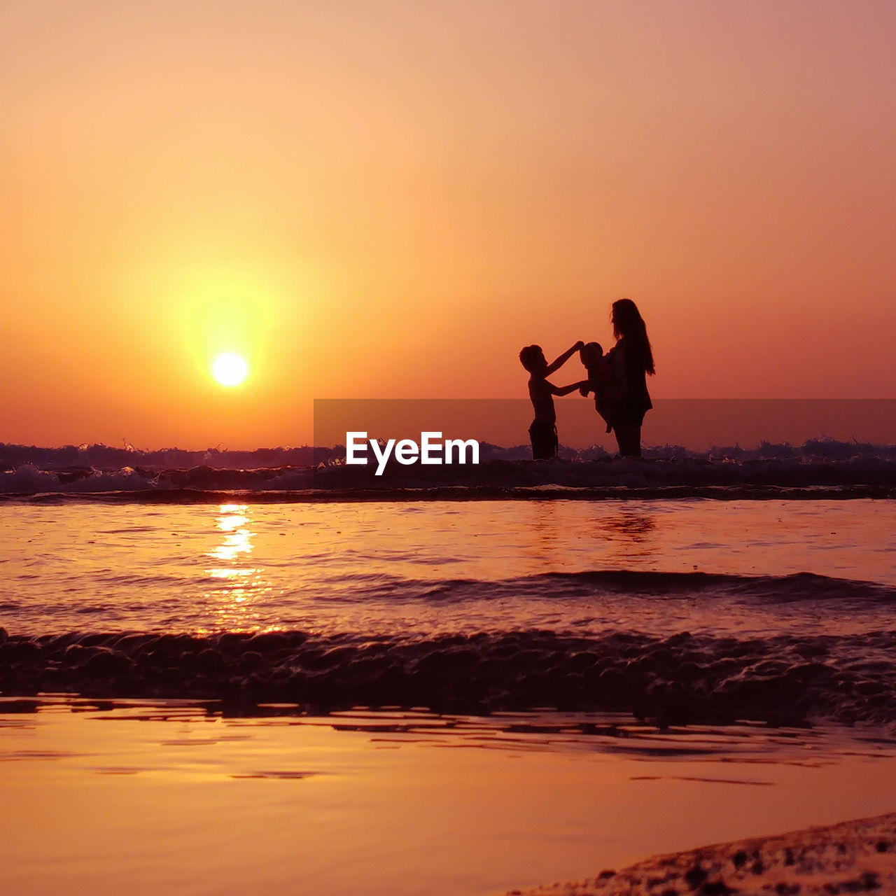sunset, two people, water, sky, silhouette, real people, orange color, togetherness, beauty in nature, sea, men, scenics - nature, standing, beach, sun, land, bonding, love, leisure activity, positive emotion, couple - relationship, outdoors