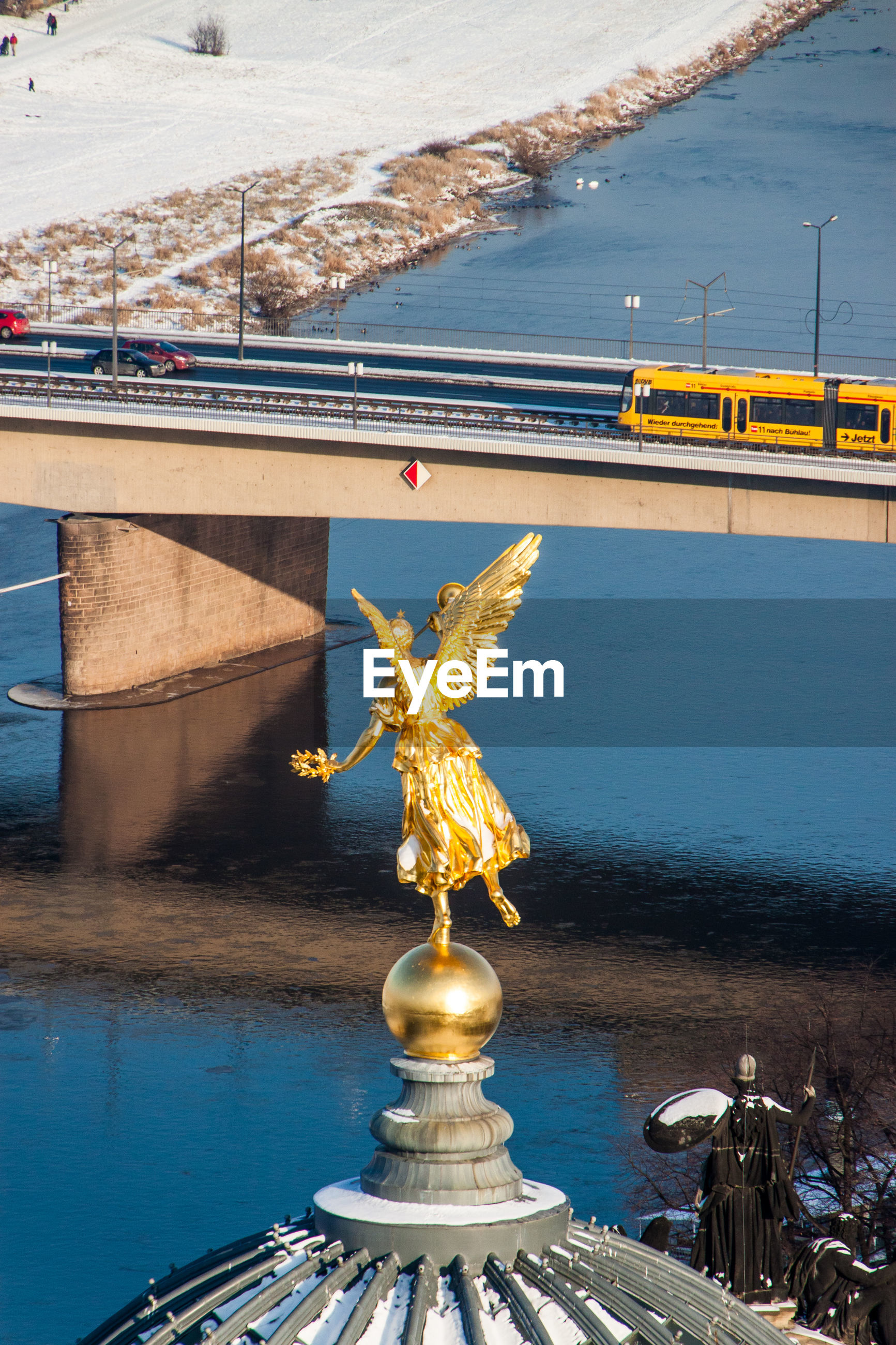 Gold angel statue on academy of fine arts dresden dome against river