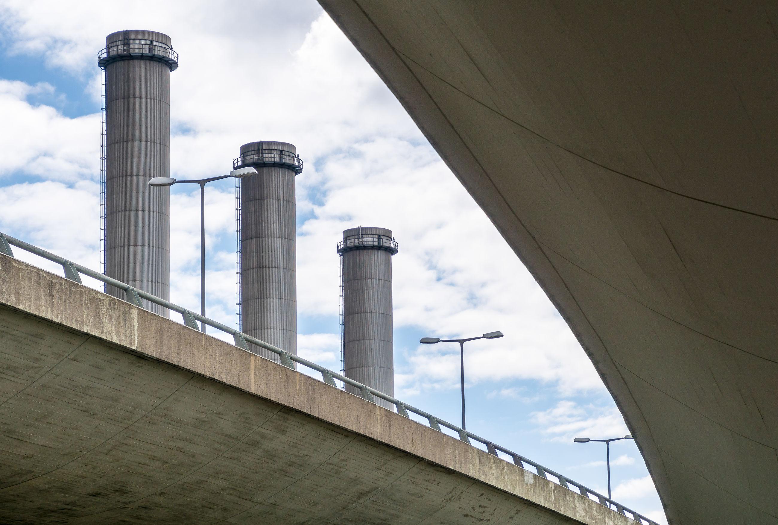 Low angle view of bridge against smoke stacks