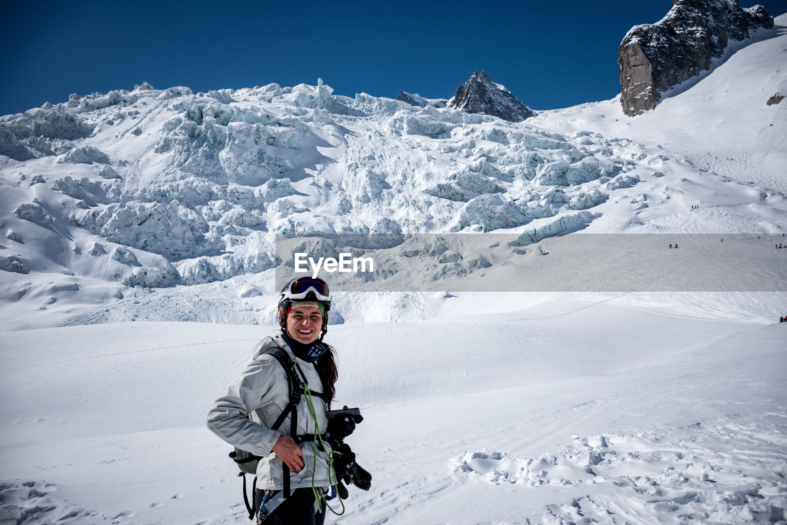 Portrait of mid adult woman standing on snowcapped mountain