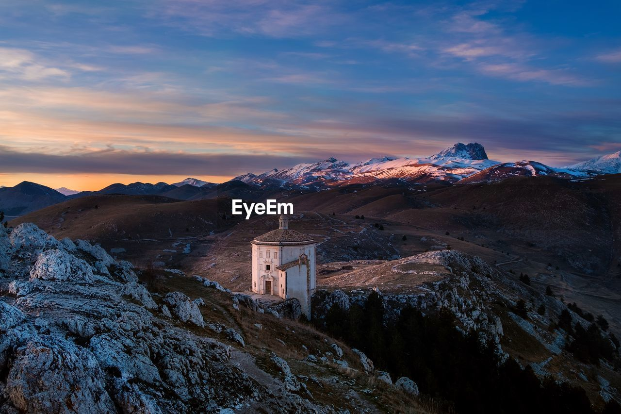 mountain, sky, cloud - sky, scenics - nature, beauty in nature, mountain range, sunset, winter, nature, tranquil scene, environment, cold temperature, snow, architecture, non-urban scene, tranquility, no people, built structure, idyllic, snowcapped mountain, mountain peak, formation