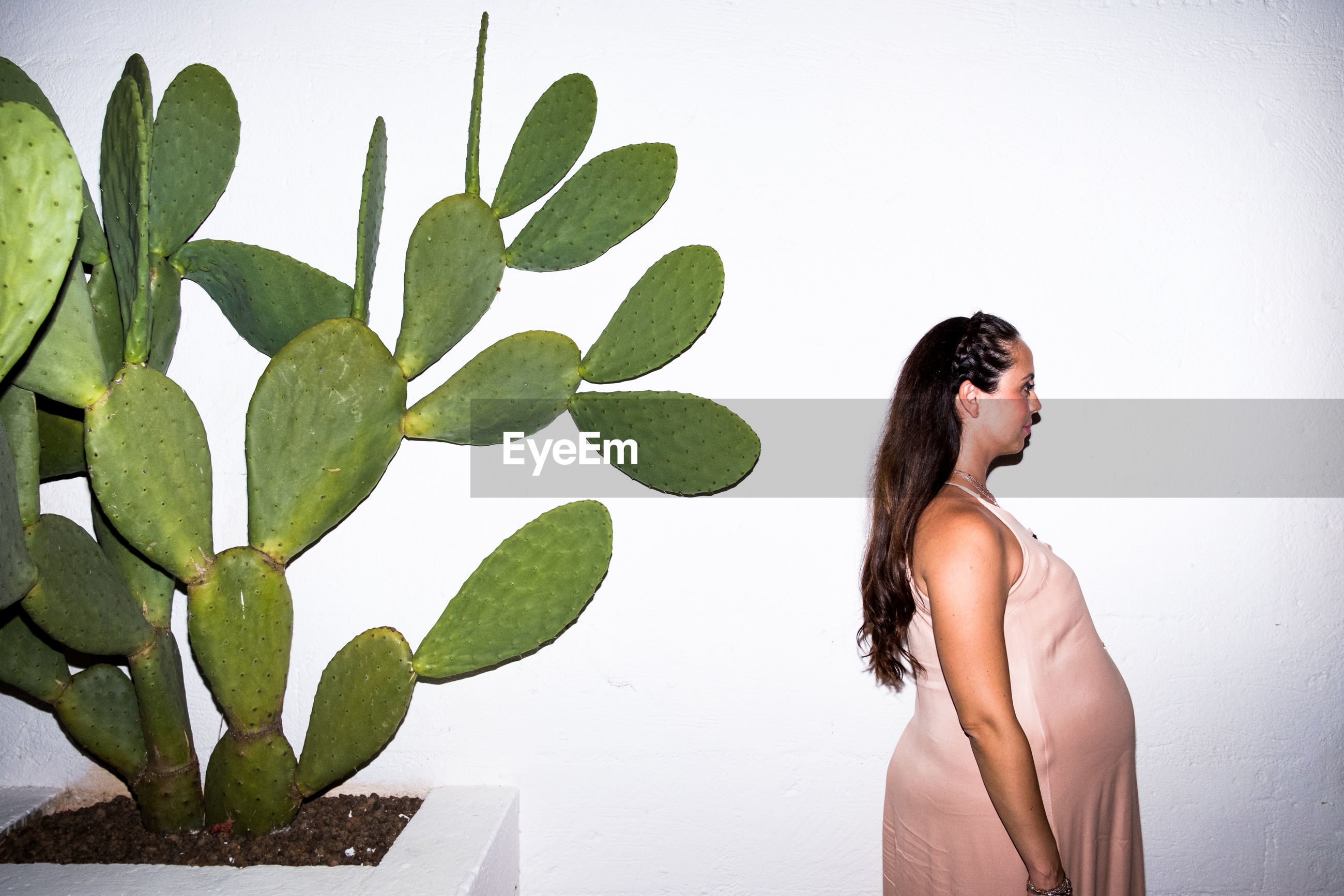 SIDE VIEW OF WOMAN STANDING BY WALL