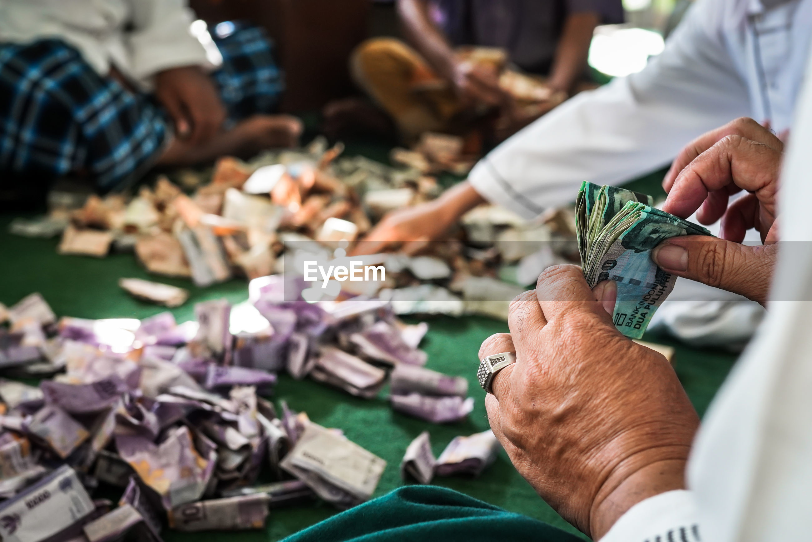 Midsection of people counting banknotes