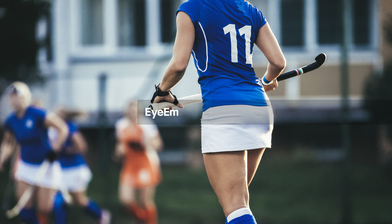 Midsection Of Hockey Player Holding Bat While Walking In Stadium