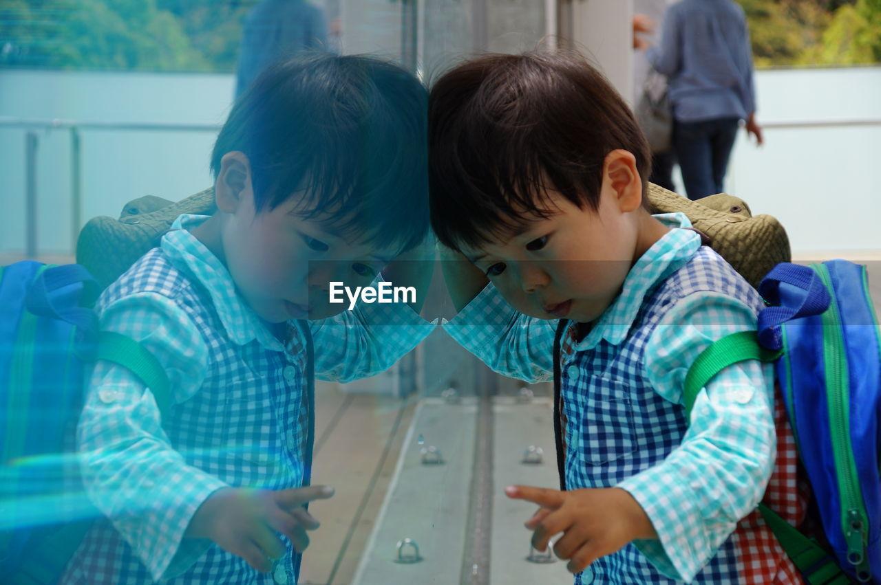 Cute boy in school uniform reflecting on glass wall