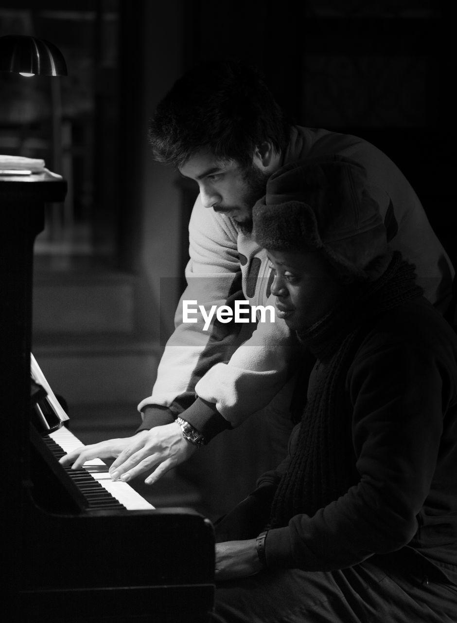 Young Male Musician Teaching Piano To Woman