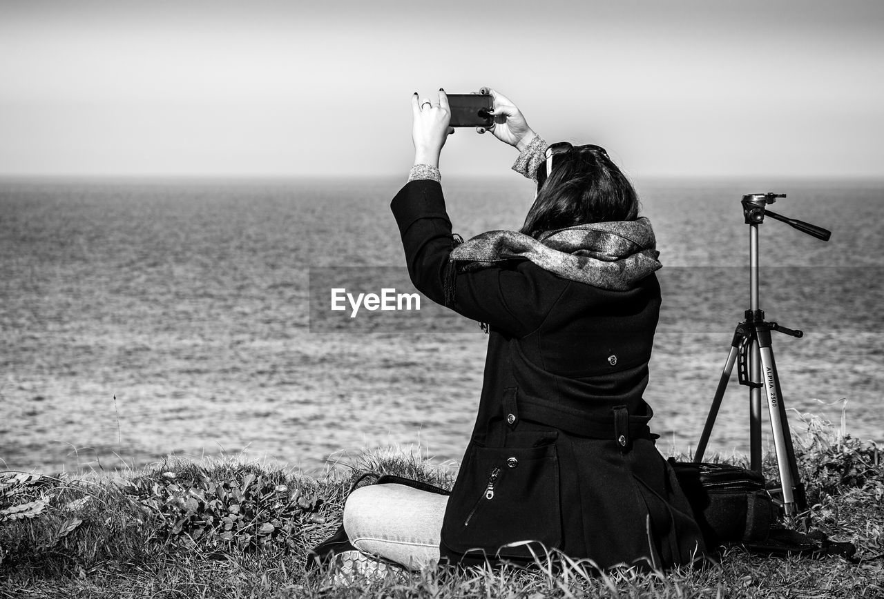 Rear View Of Woman Photographing Sea Through Smart Phone