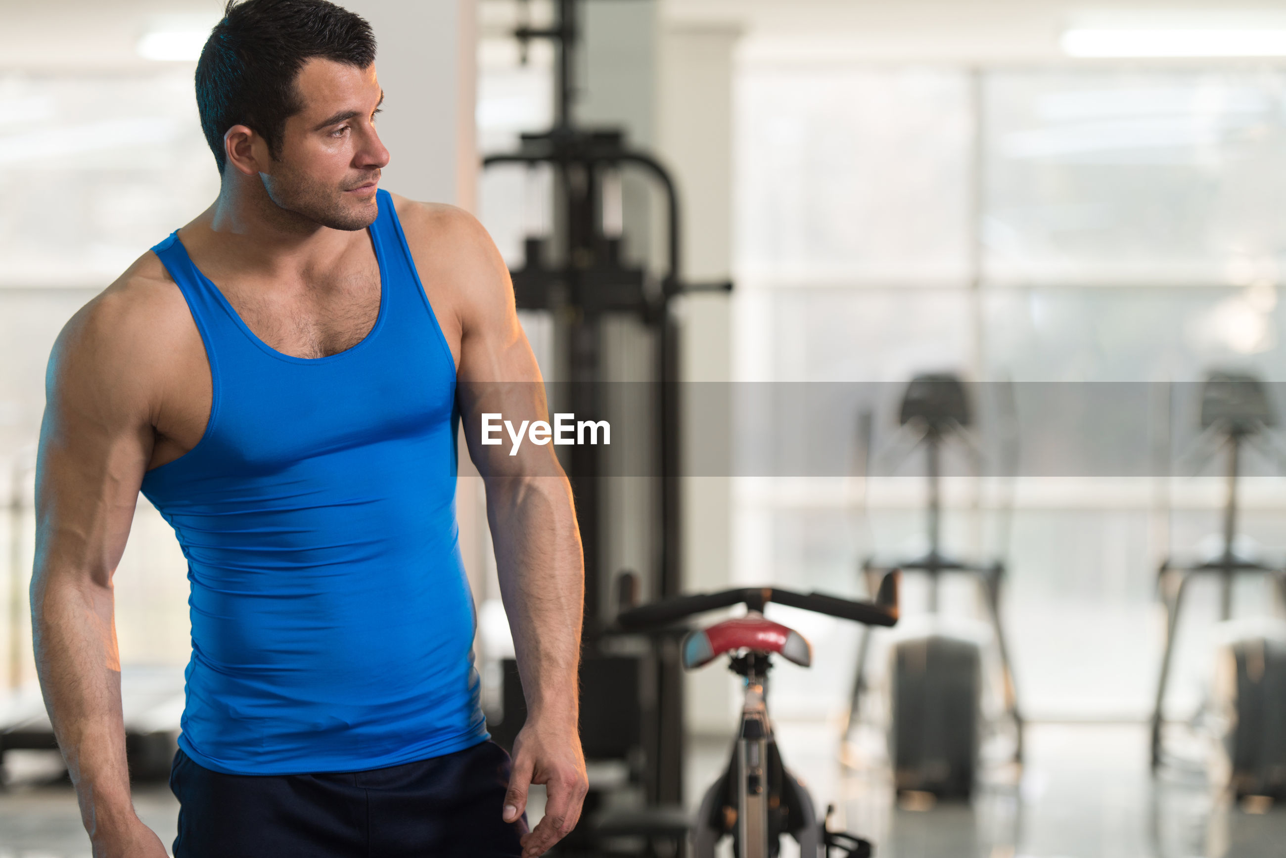 Muscular man wearing vest standing in gym