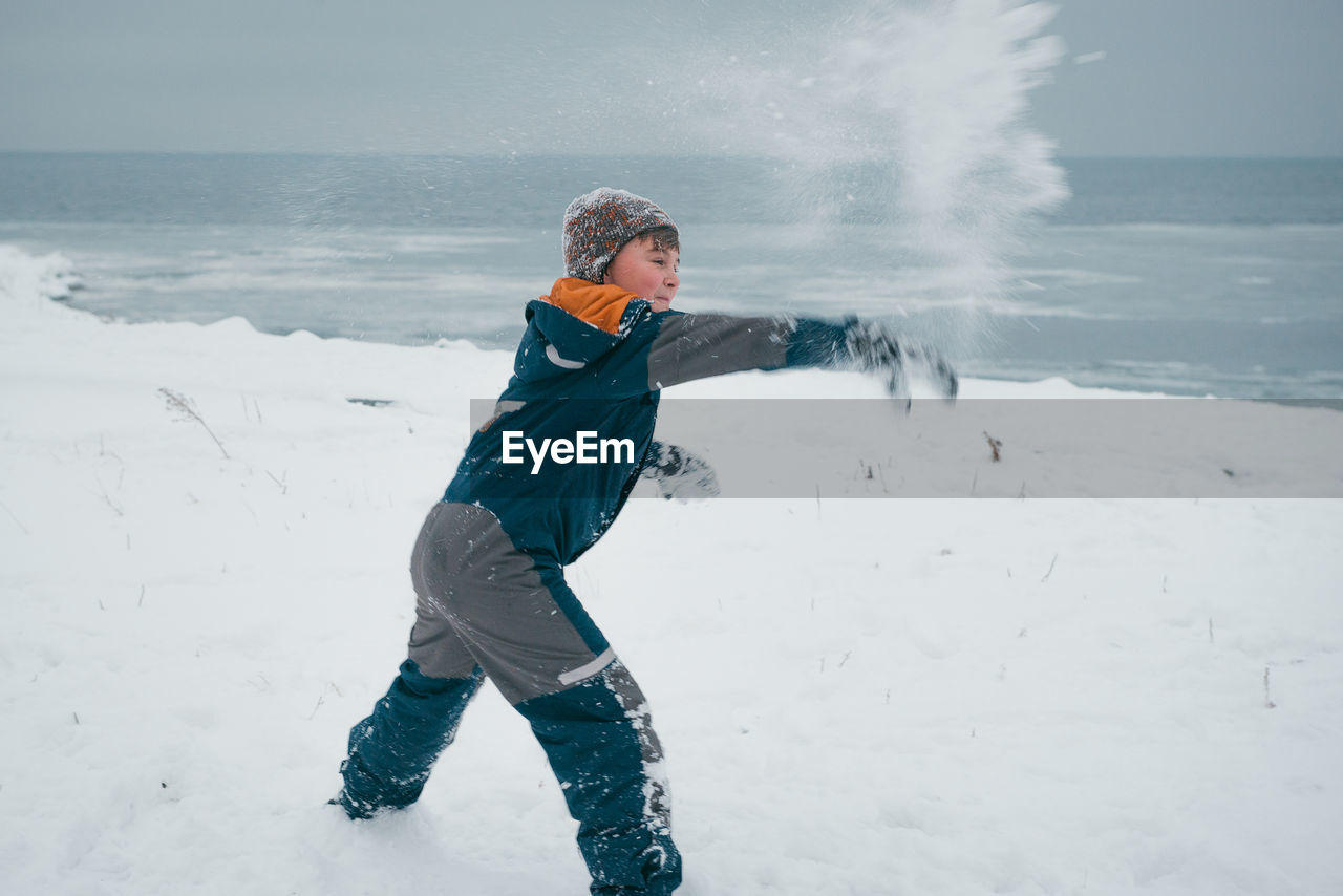Side View Of Playful Boy Throwing Snow During Winter