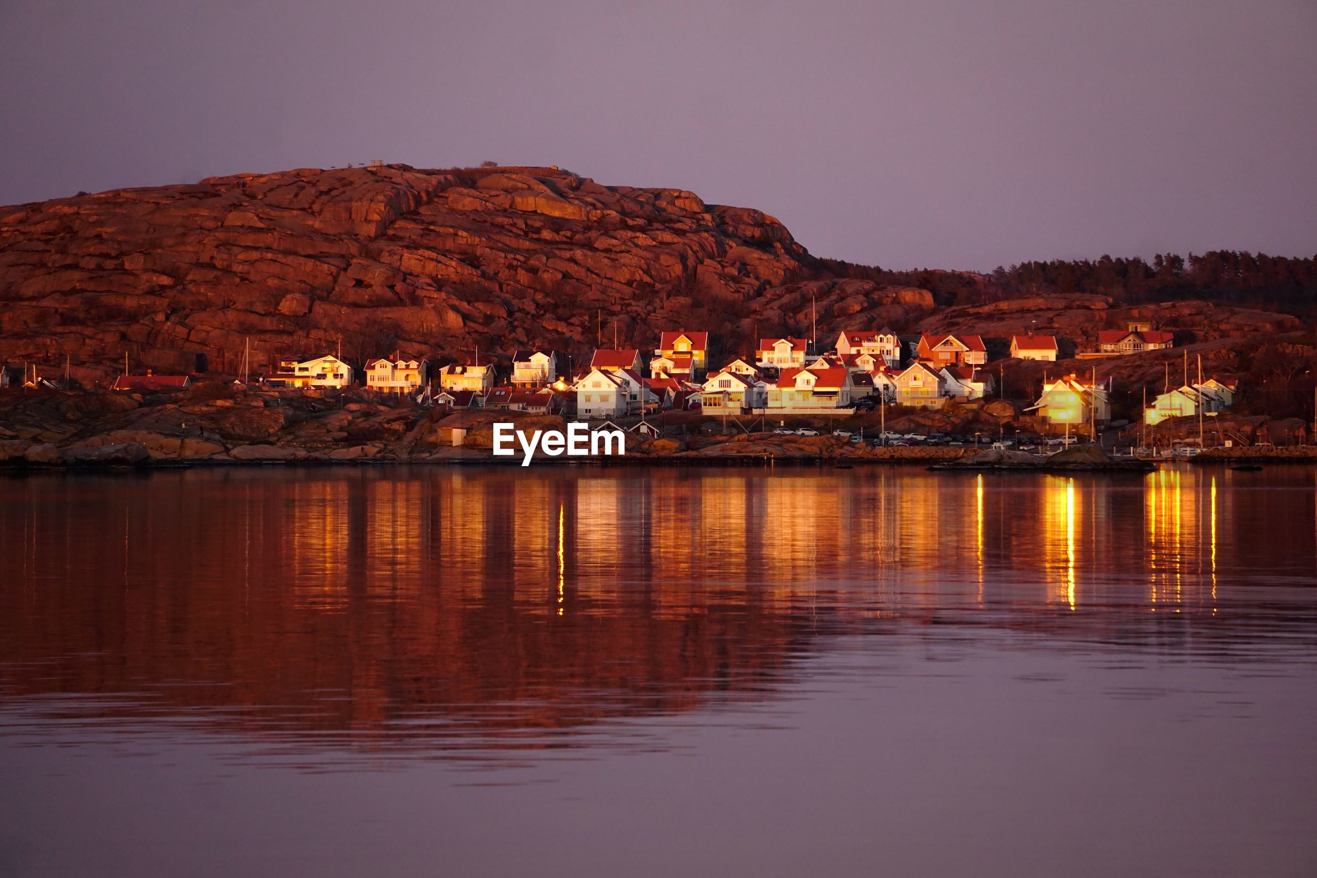 LAKE BY ILLUMINATED BUILDINGS AGAINST CLEAR SKY