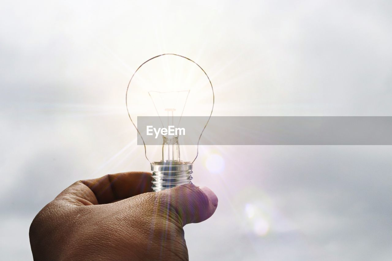 human body part, human hand, hand, light bulb, finger, holding, human finger, glass - material, lighting equipment, body part, one person, transparent, unrecognizable person, sky, real people, electricity, focus on foreground, nature, close-up, filament, light, glass, power supply