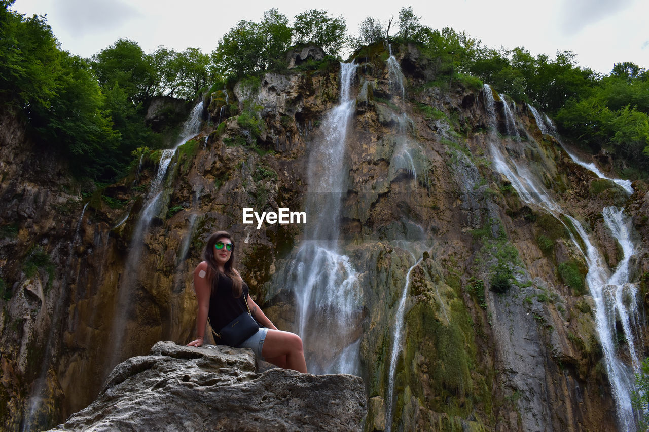 Low angle portrait of mid adult woman wearing sunglasses sitting on rock against waterfall