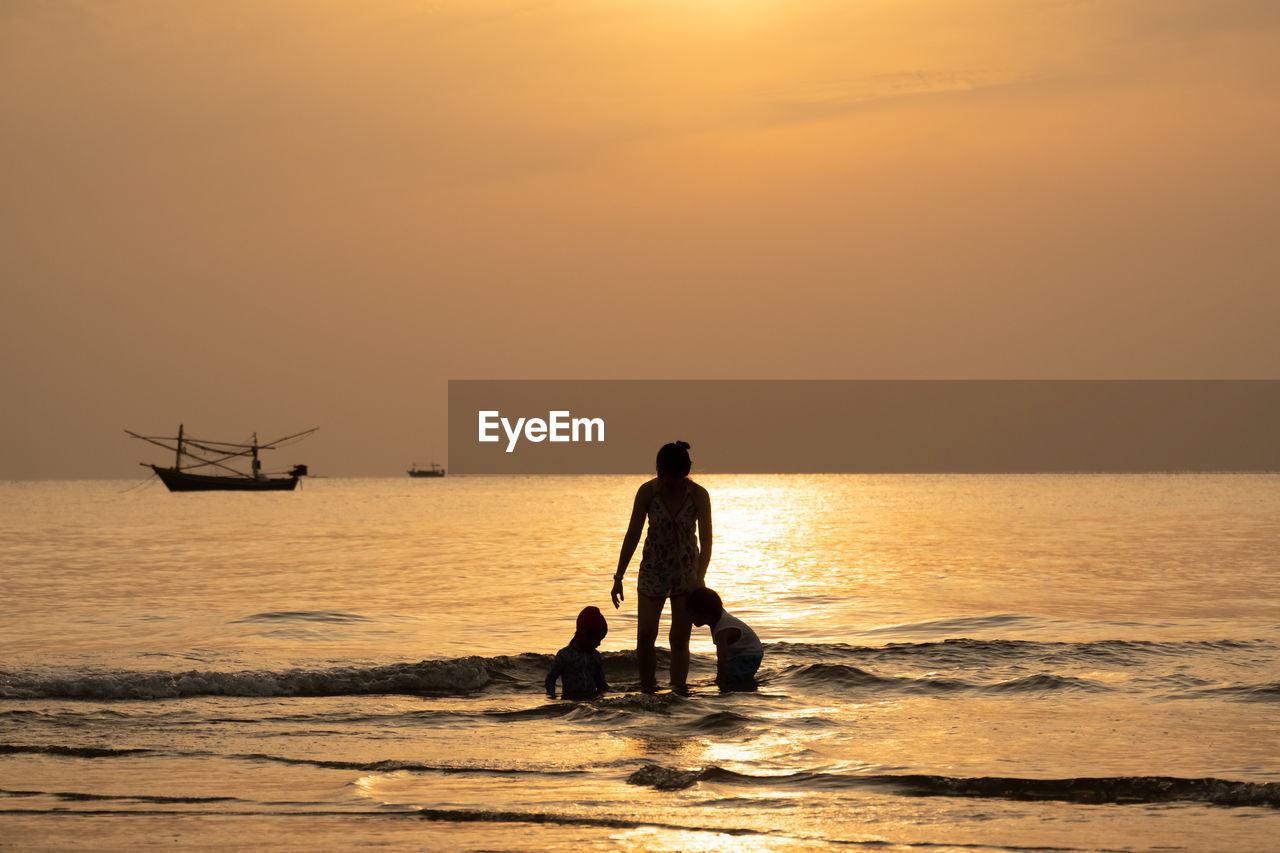 Silhouette mother with children standing in sea during sunset