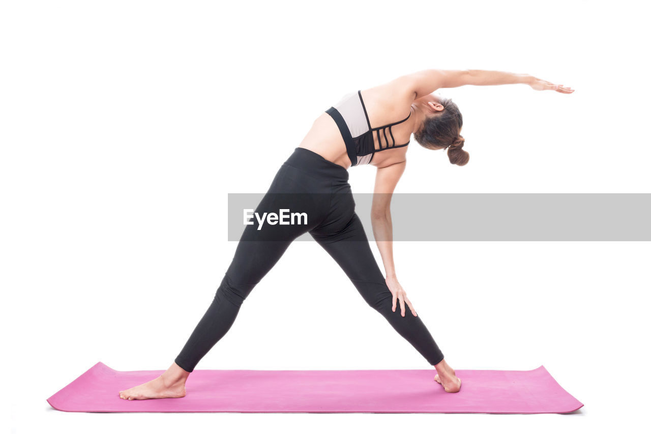 Young woman exercising against white background