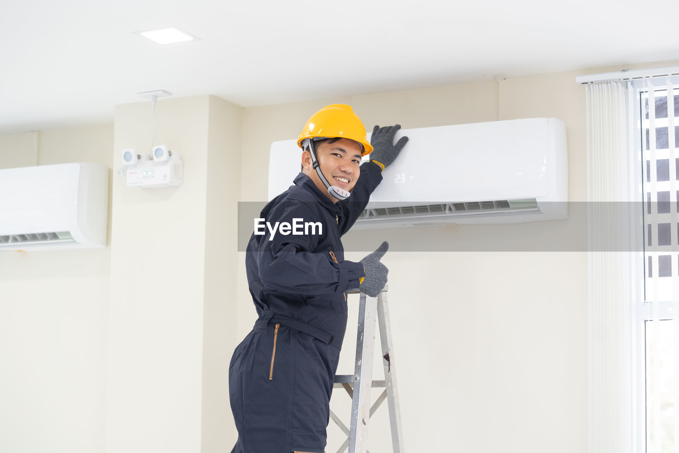 Portrait of man repairing air conditioner at home