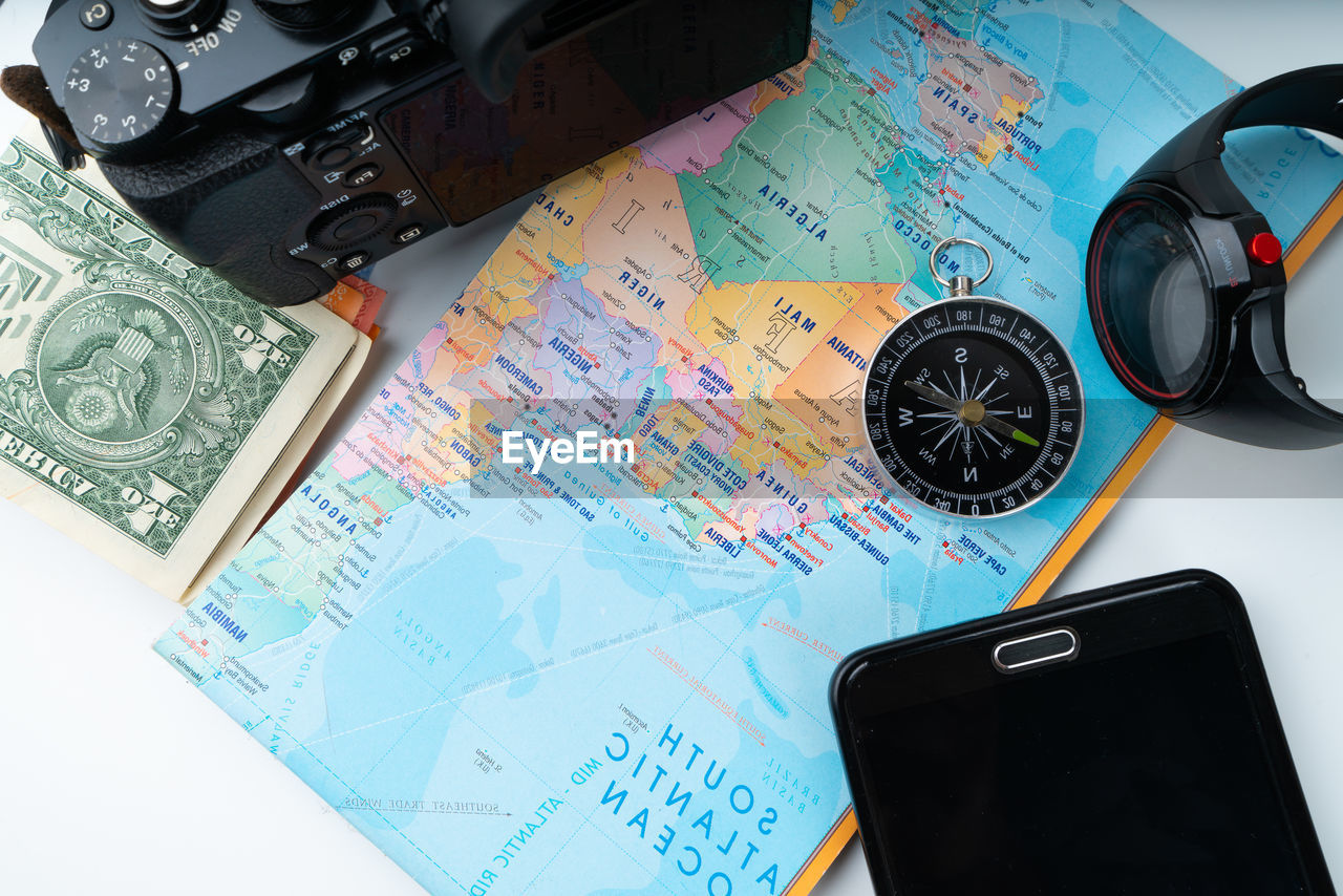 High angle view of map with camera and mobile phone on white background