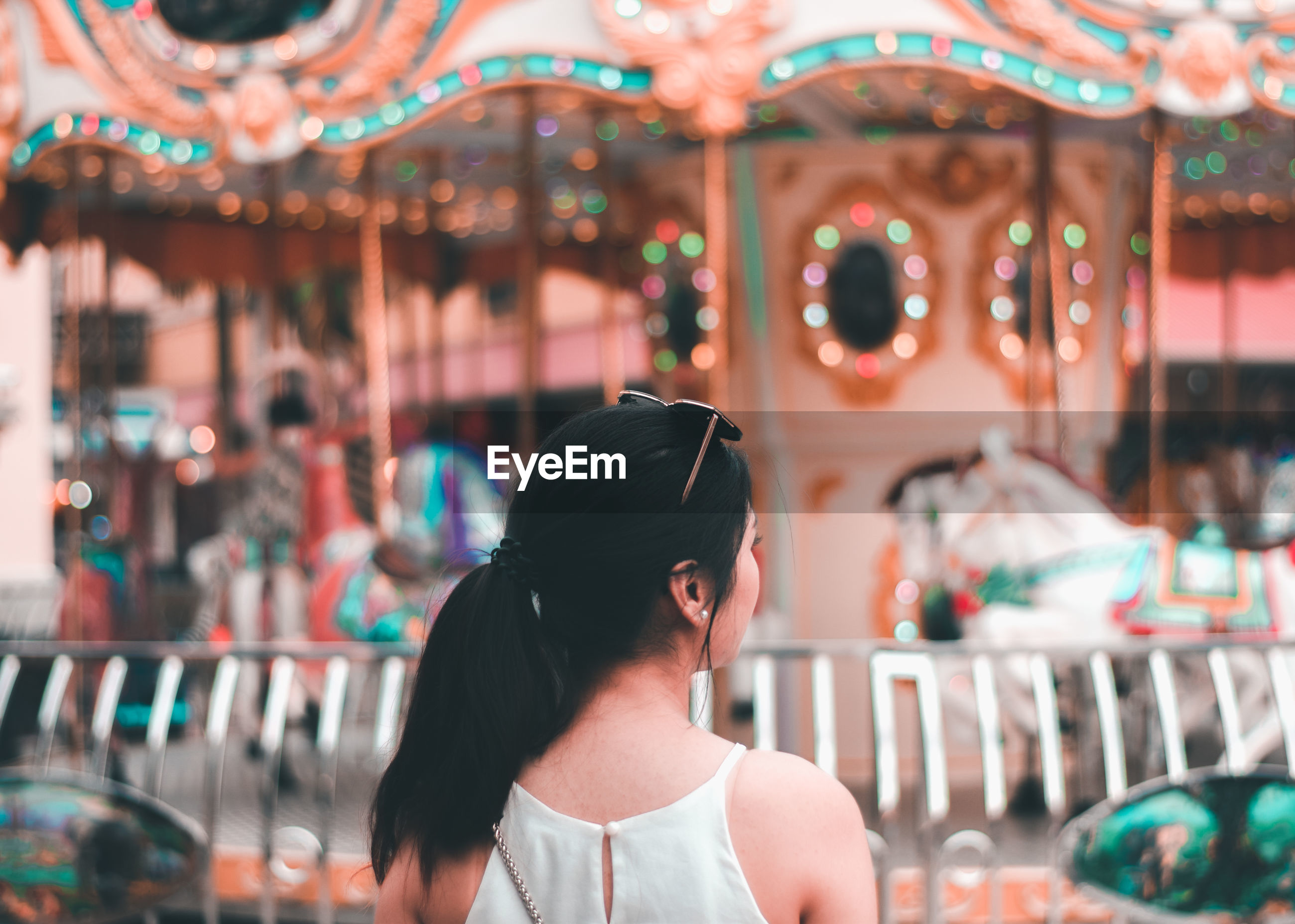 Rear view of woman against carousel in amusement park
