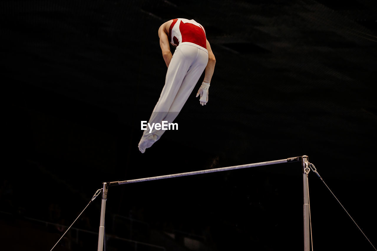 Low angle view of athlete performing acrobatics in gym