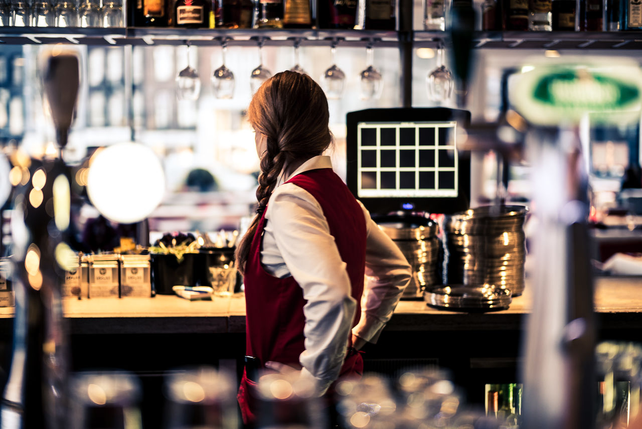 Side View Of Bartender Standing With Hands On Hip At Nightclub
