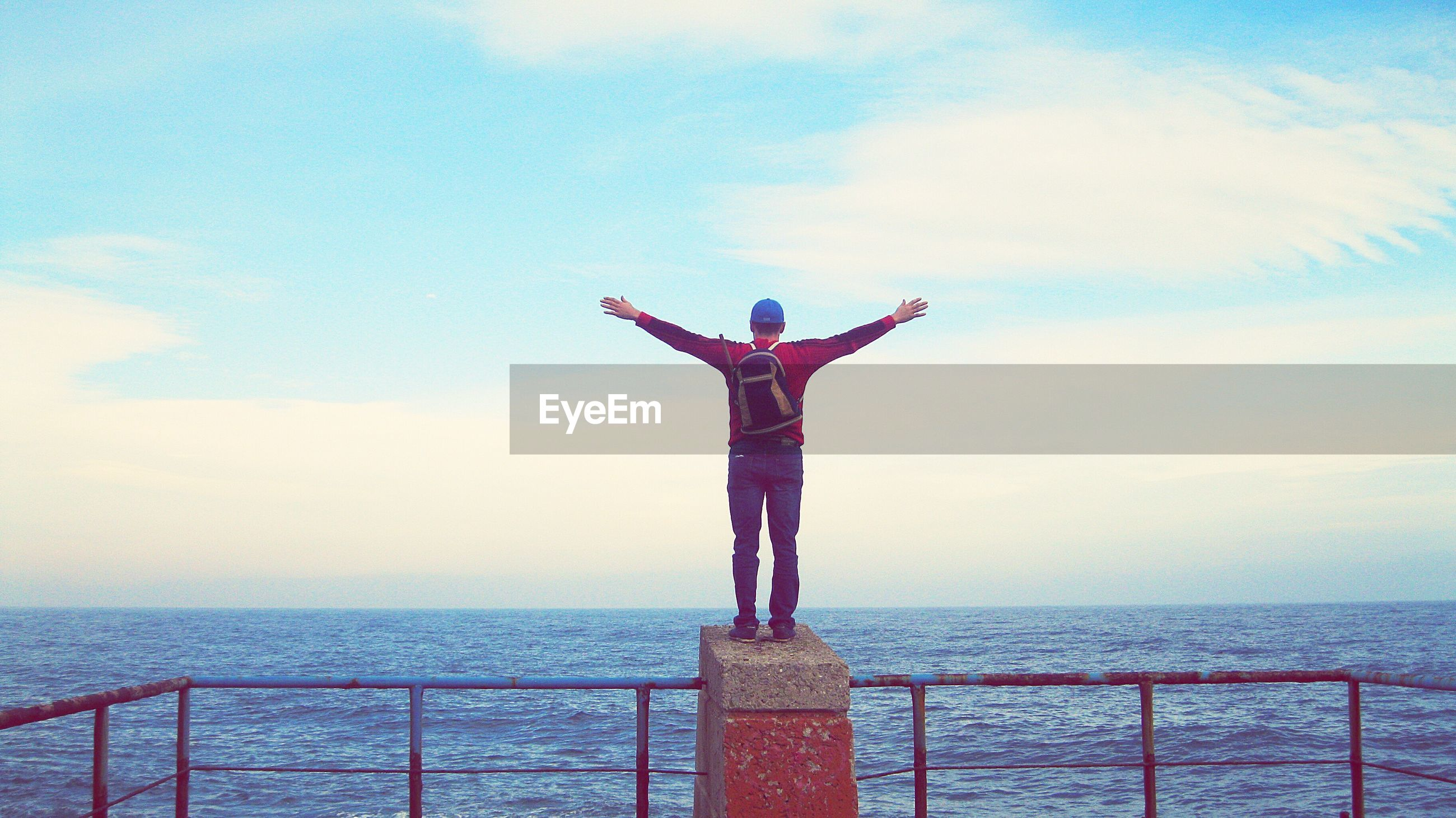 Man standing on railing over sea against sky