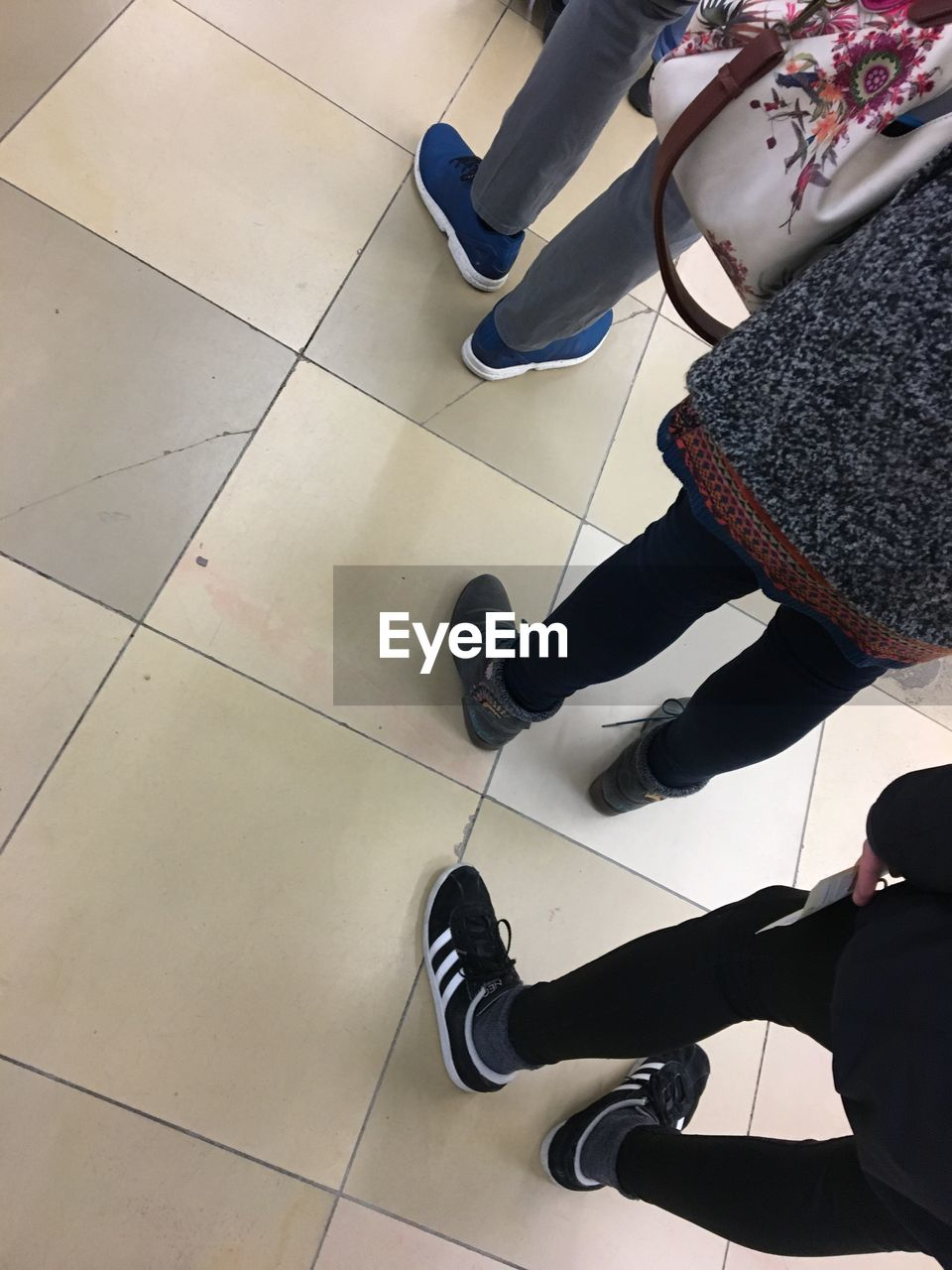 tiled floor, real people, low section, shoe, high angle view, sitting, indoors, human leg, standing, lifestyles, women, day, one person, people