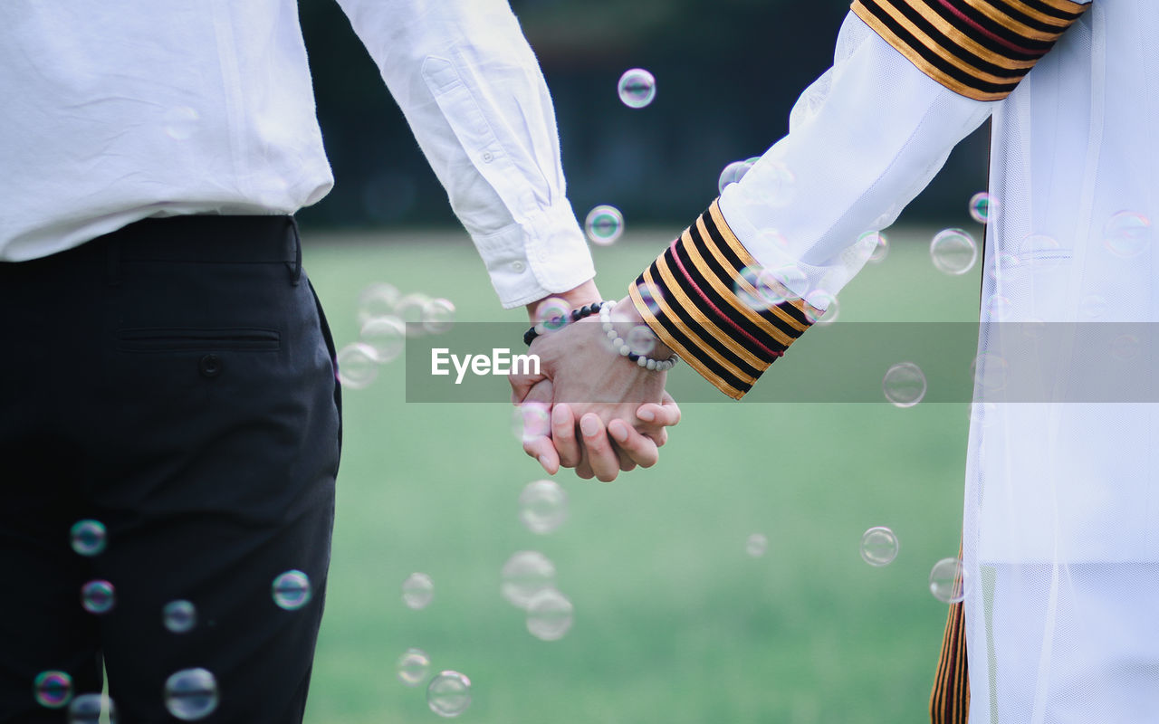 Midsection of couple holding hands amidst bubbles