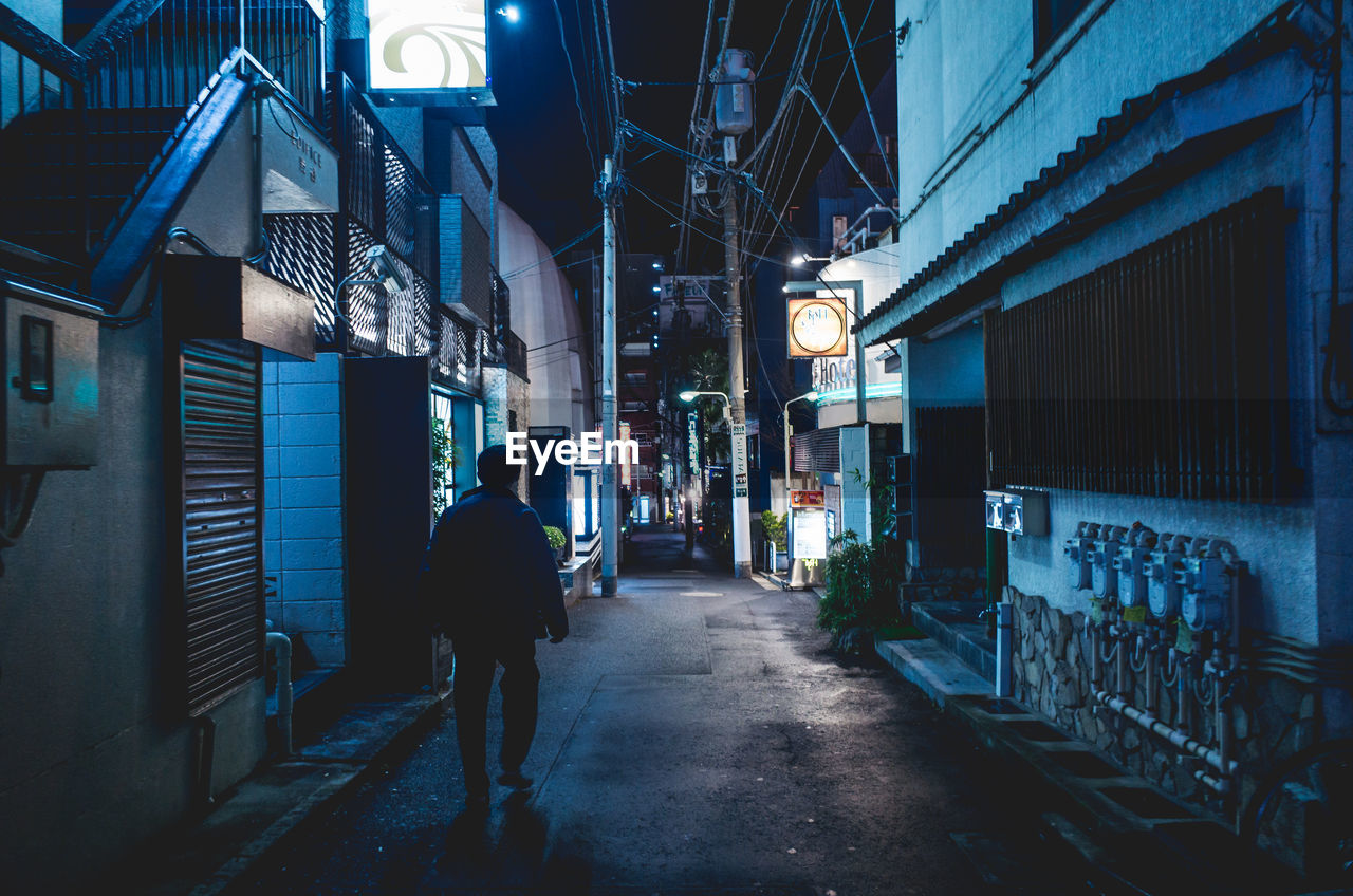 architecture, built structure, building exterior, night, illuminated, city, real people, the way forward, walking, lighting equipment, direction, street, lifestyles, men, rear view, building, people, footpath, full length, outdoors, alley