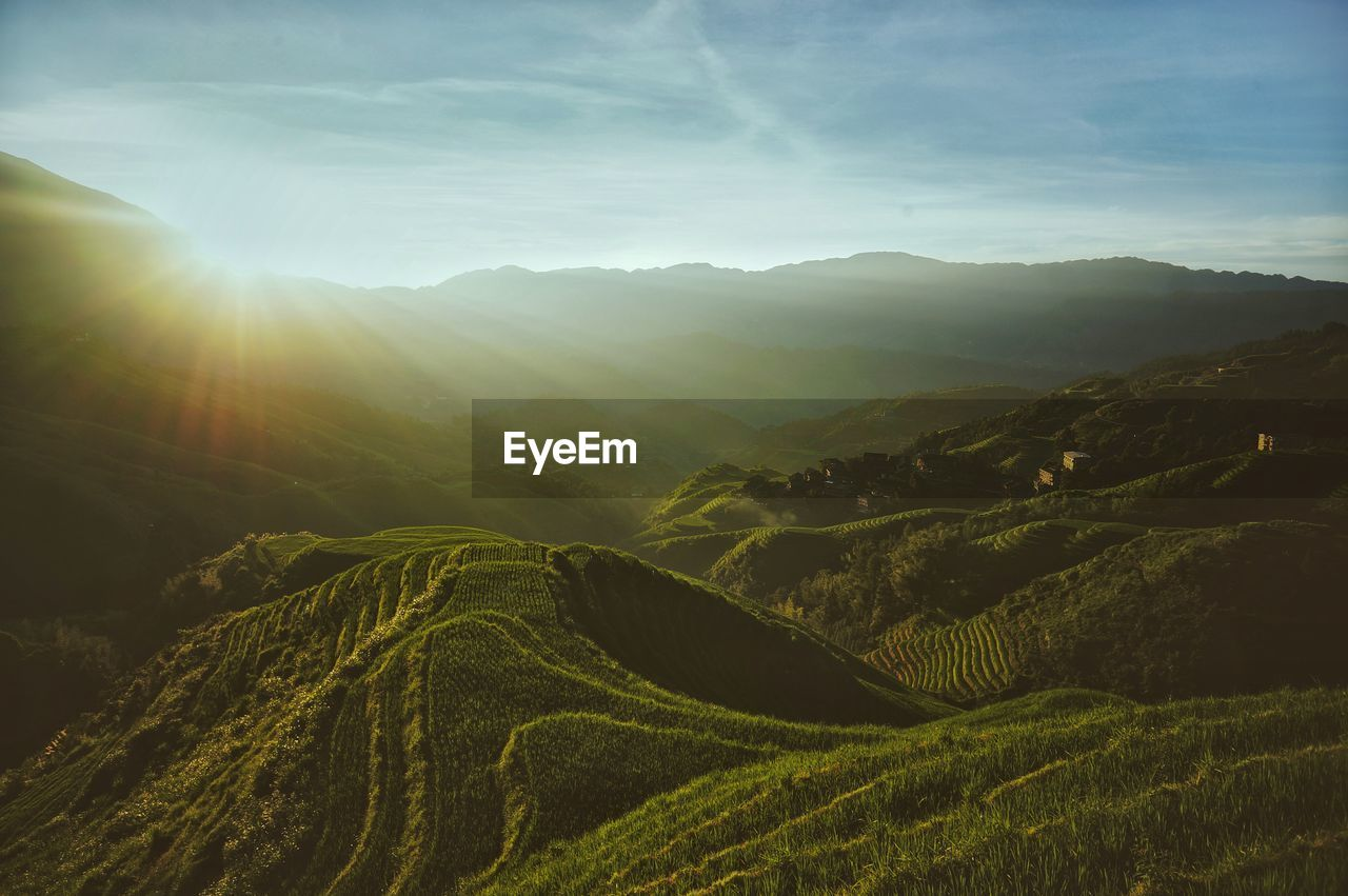 Scenic View Of Rice Terraces Against Cloudy Sky During Sunrise