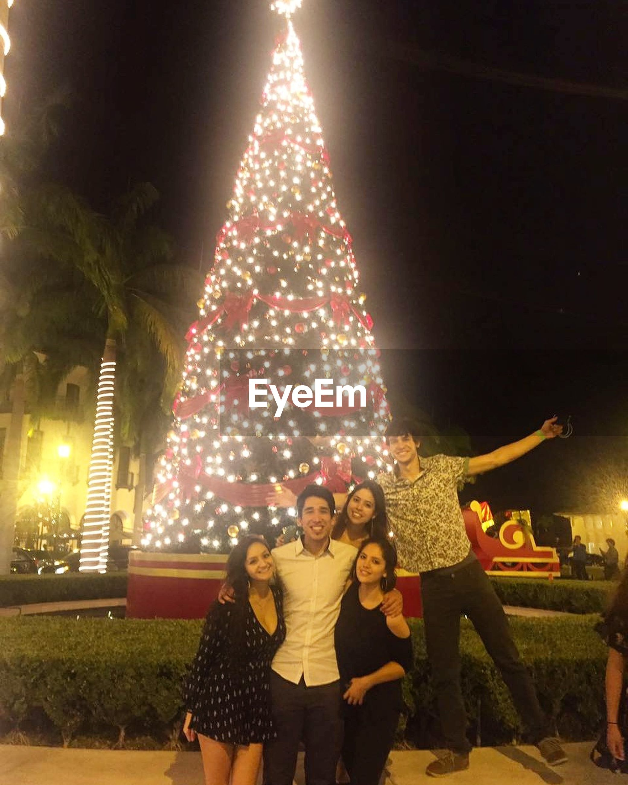 illuminated, celebration, night, christmas, real people, christmas tree, togetherness, christmas decoration, enjoyment, leisure activity, christmas lights, happiness, outdoors, lifestyles, standing, vacations, tree, friendship, young women, young adult, architecture
