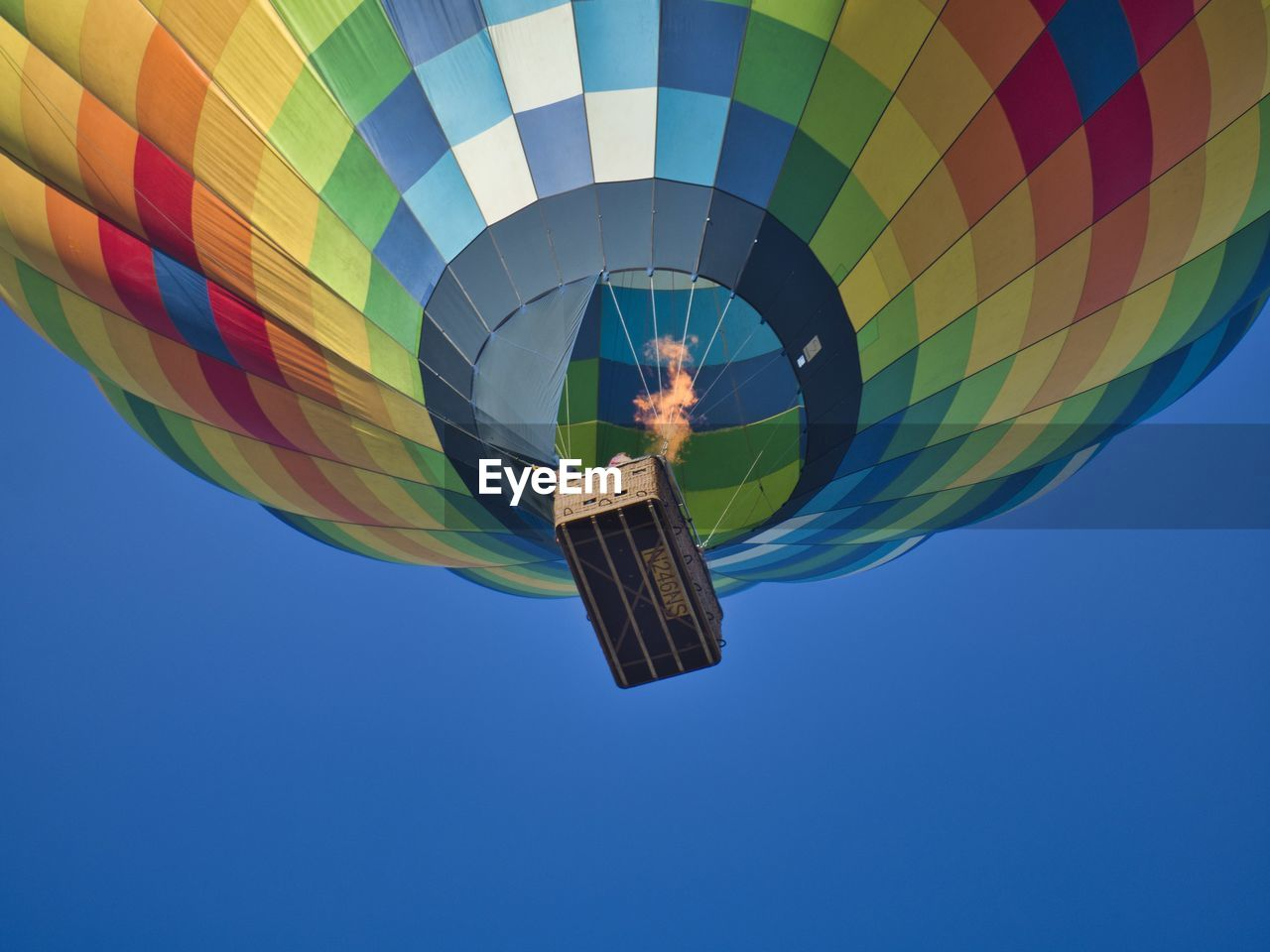 Low angle view of hot air balloon flying against clear blue sky