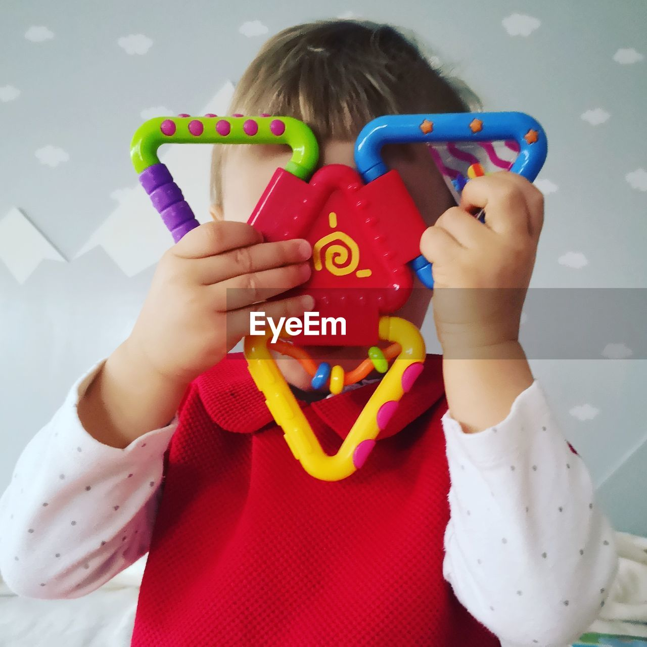 childhood, child, one person, real people, multi colored, leisure activity, front view, indoors, toy, red, boys, lifestyles, casual clothing, holding, males, playing, girls, females, innocence, obscured face