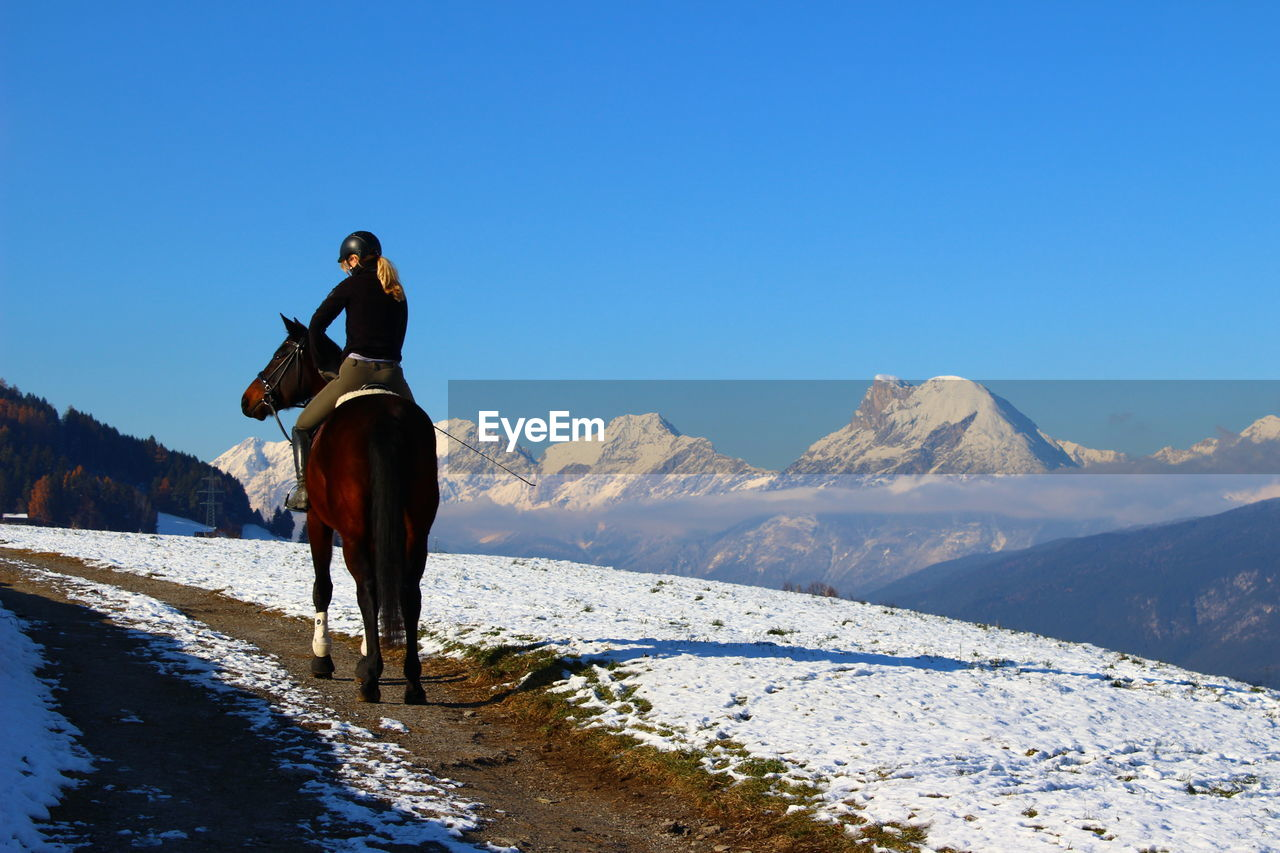 Rear View Of Woman Riding Horse On Snow Covered Mountain Against Clear Sky