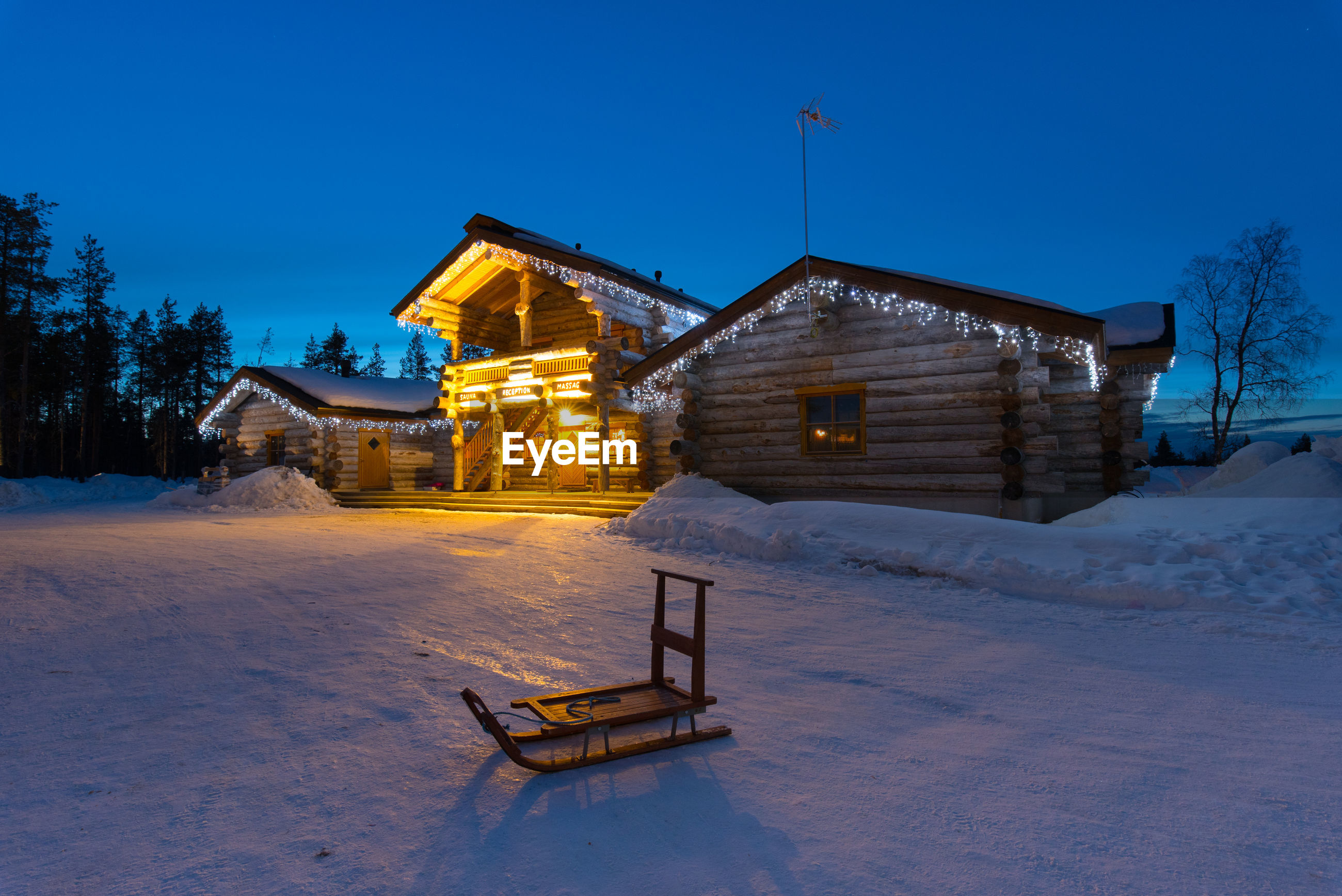 HOUSE ON SNOW COVERED FIELD AGAINST SKY AT DUSK