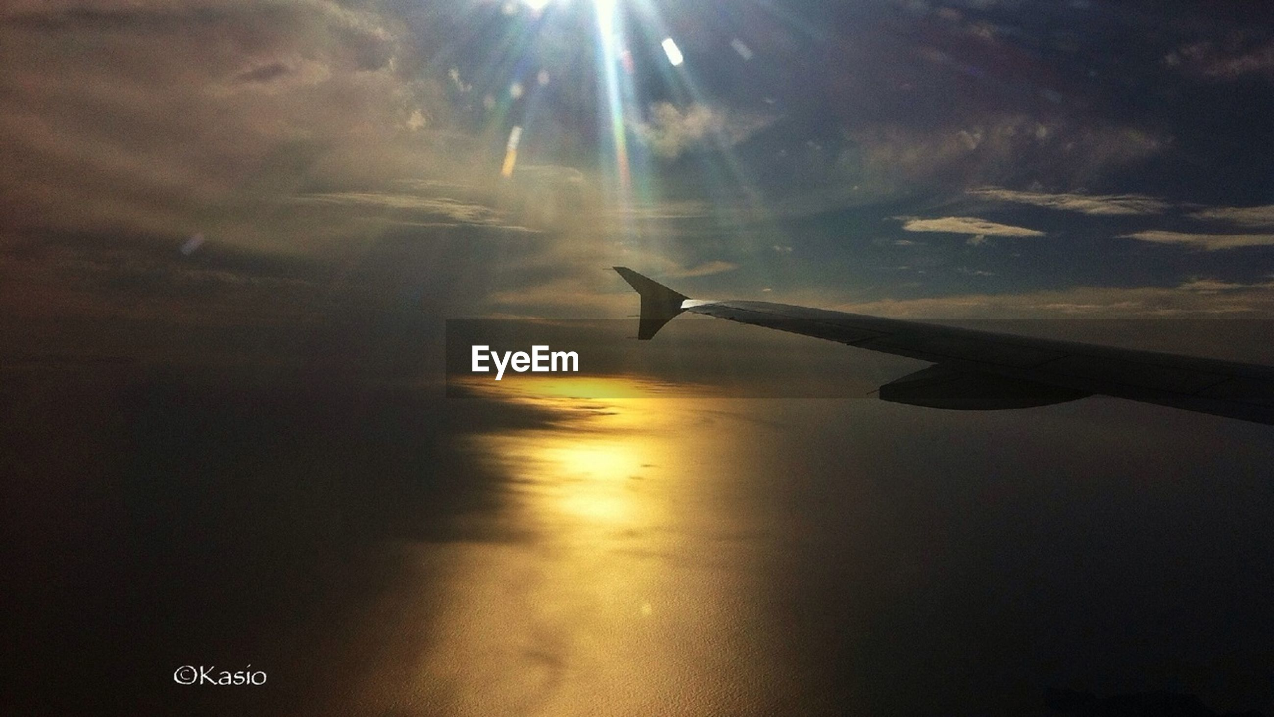 airplane, flying, transportation, aircraft wing, air vehicle, mode of transport, sun, sunset, sky, travel, mid-air, scenics, journey, on the move, sunlight, beauty in nature, nature, cloud - sky, part of, aerial view