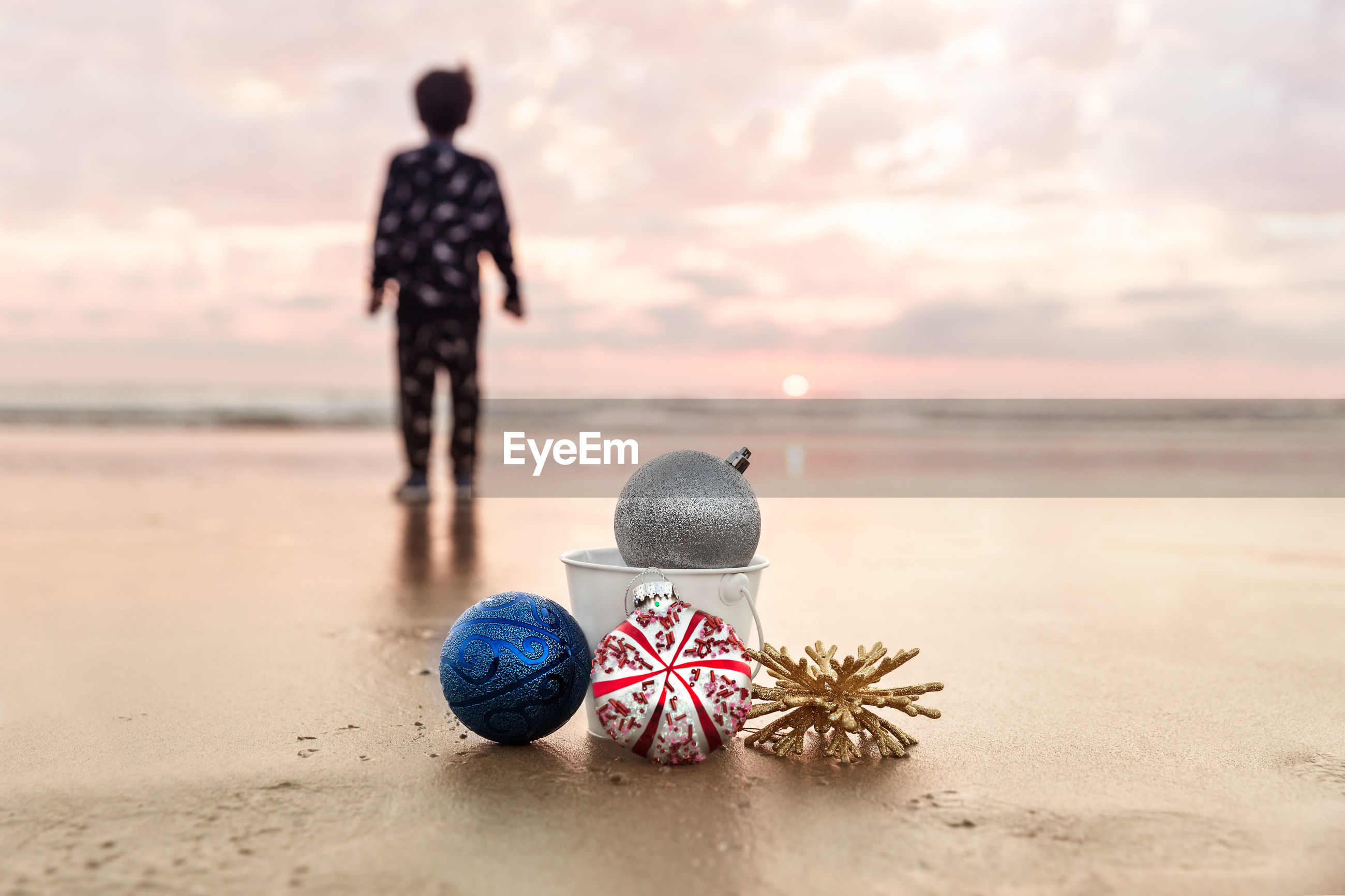 Christmas decorations against boy standing at beach during sunset