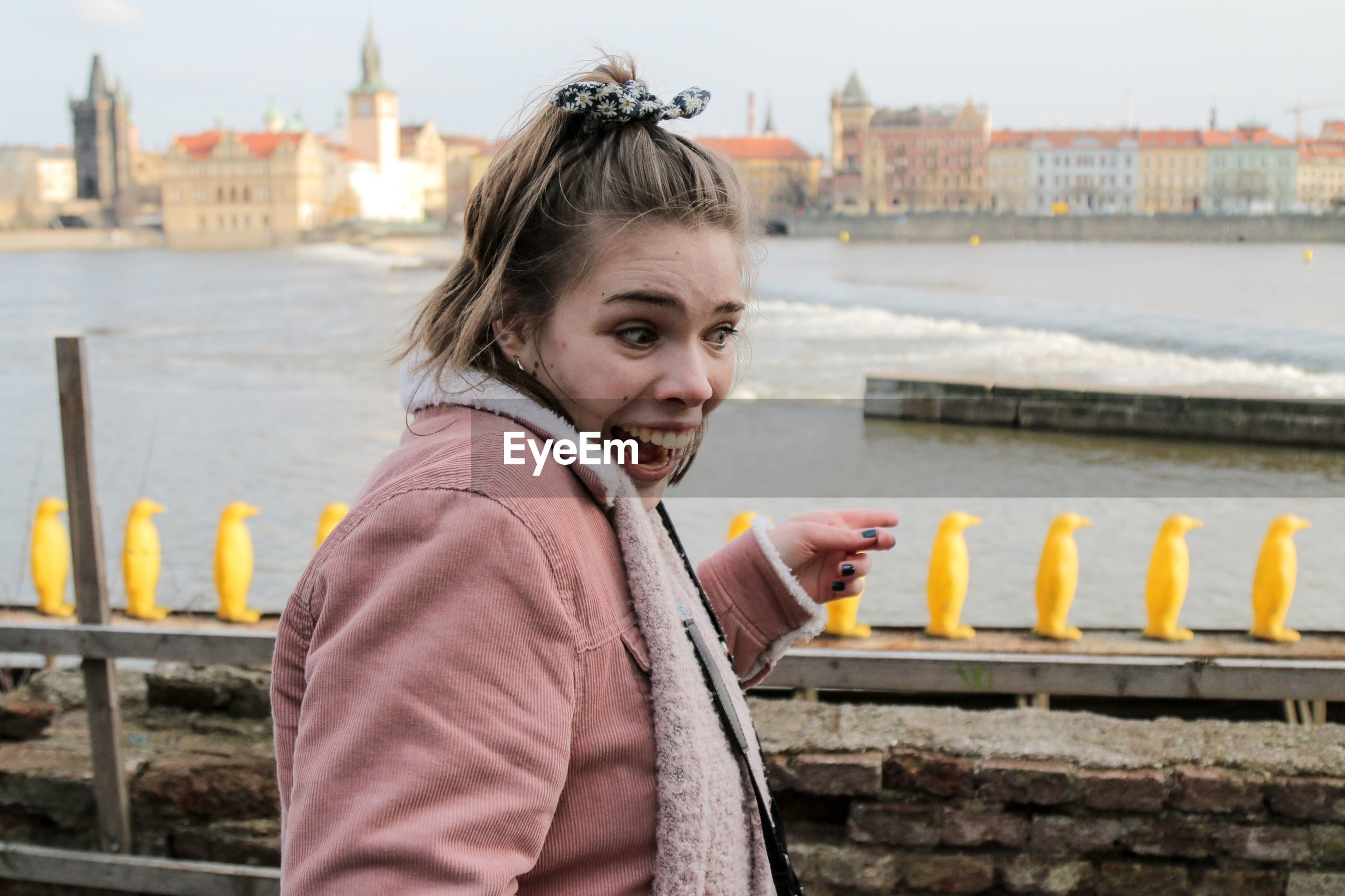 Side view of cheerful woman gesturing against river in city
