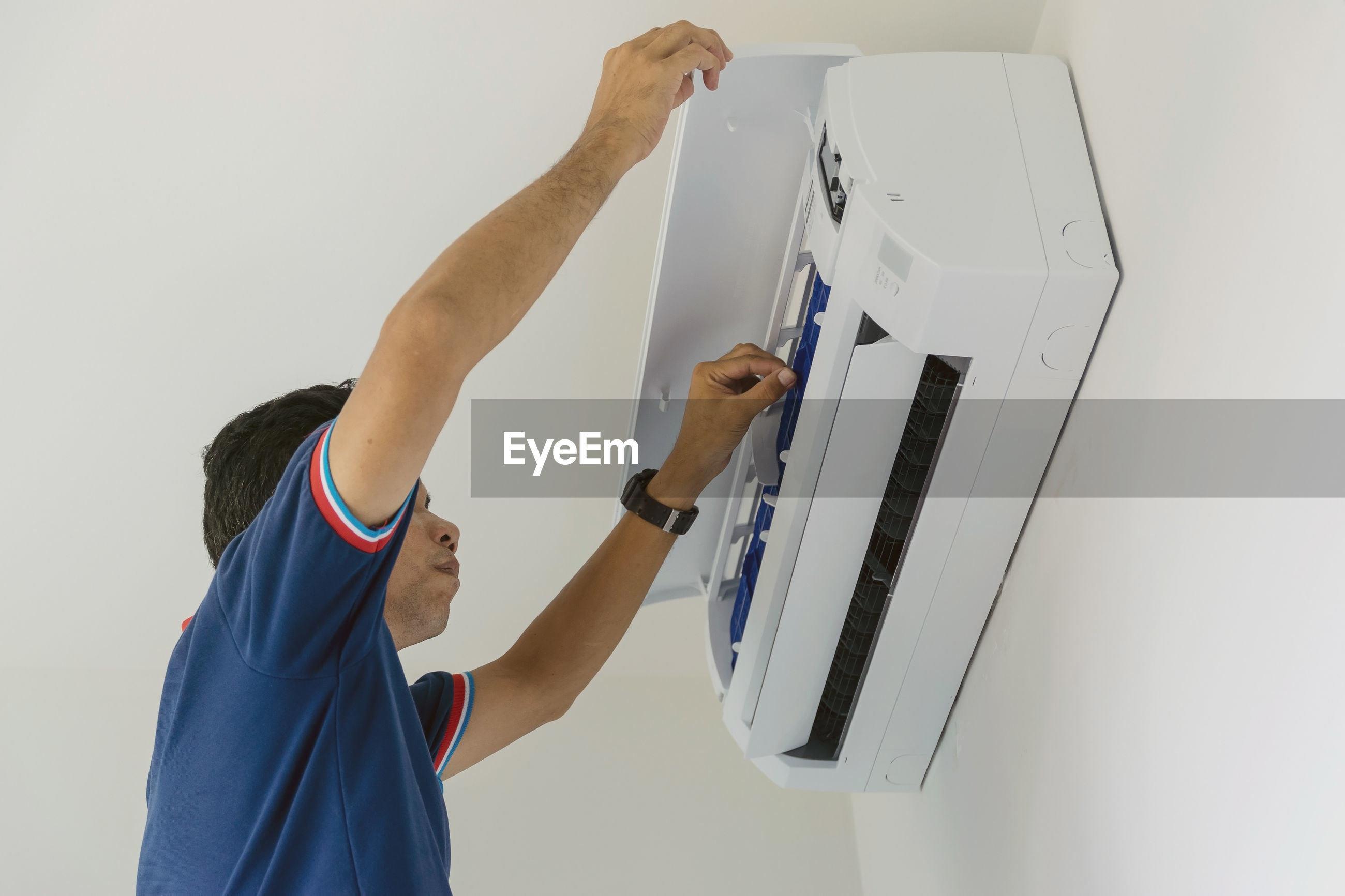 Low angle view of man repairing air conditioner on wall at home