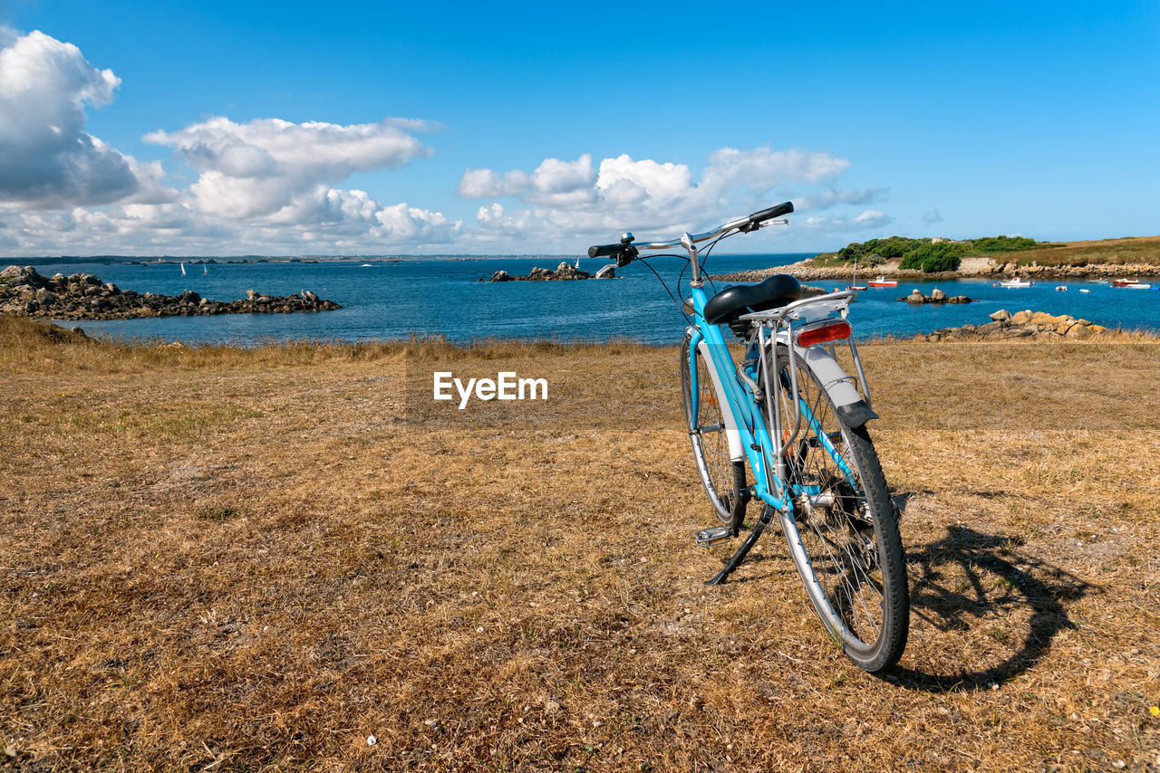 bicycle, sky, transportation, mode of transportation, land vehicle, water, land, nature, day, scenics - nature, sea, cloud - sky, stationary, horizon, beauty in nature, travel, beach, non-urban scene, no people, outdoors, horizon over water