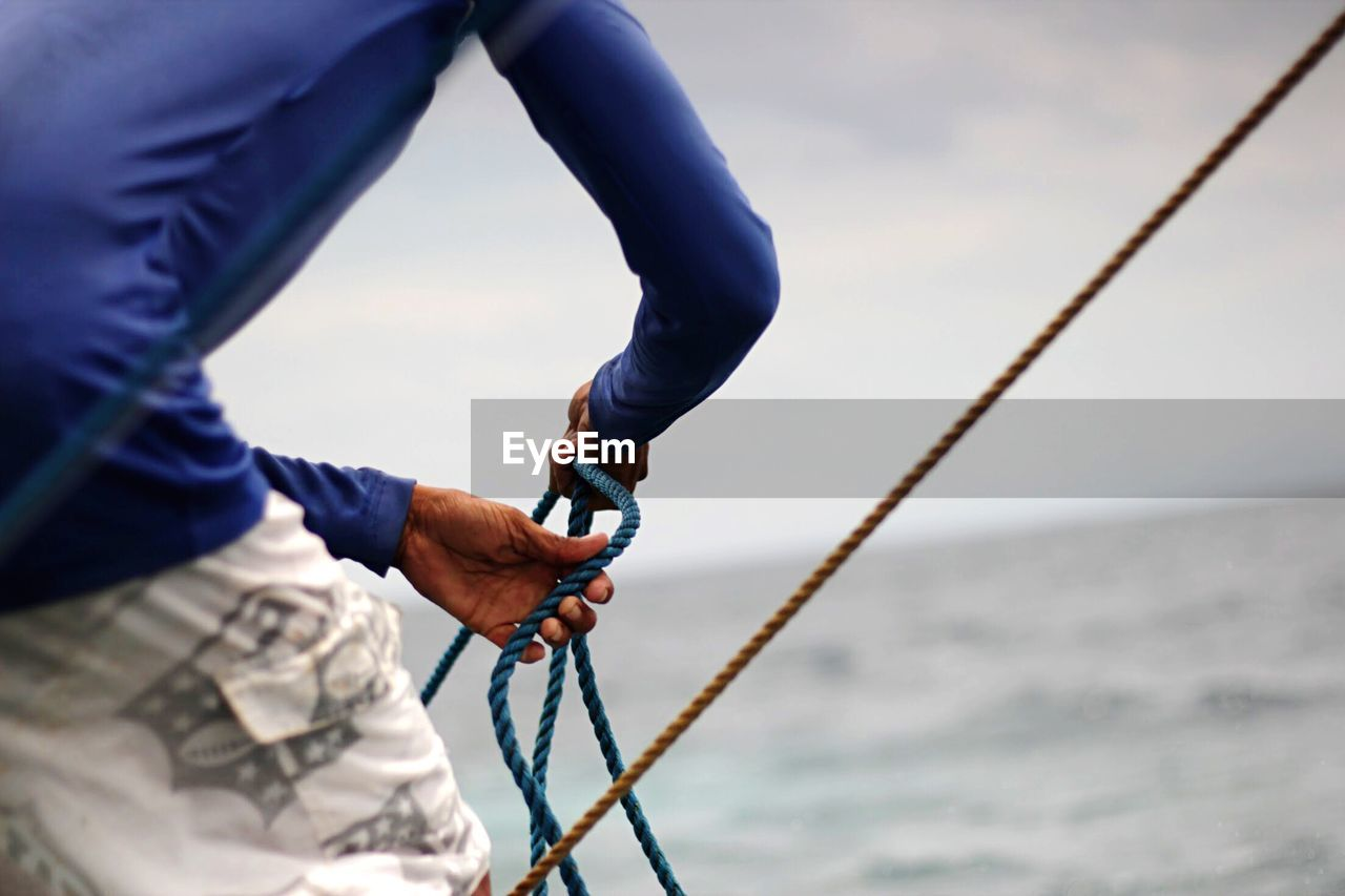 Low Section Of Man Holding Rope Against Sea