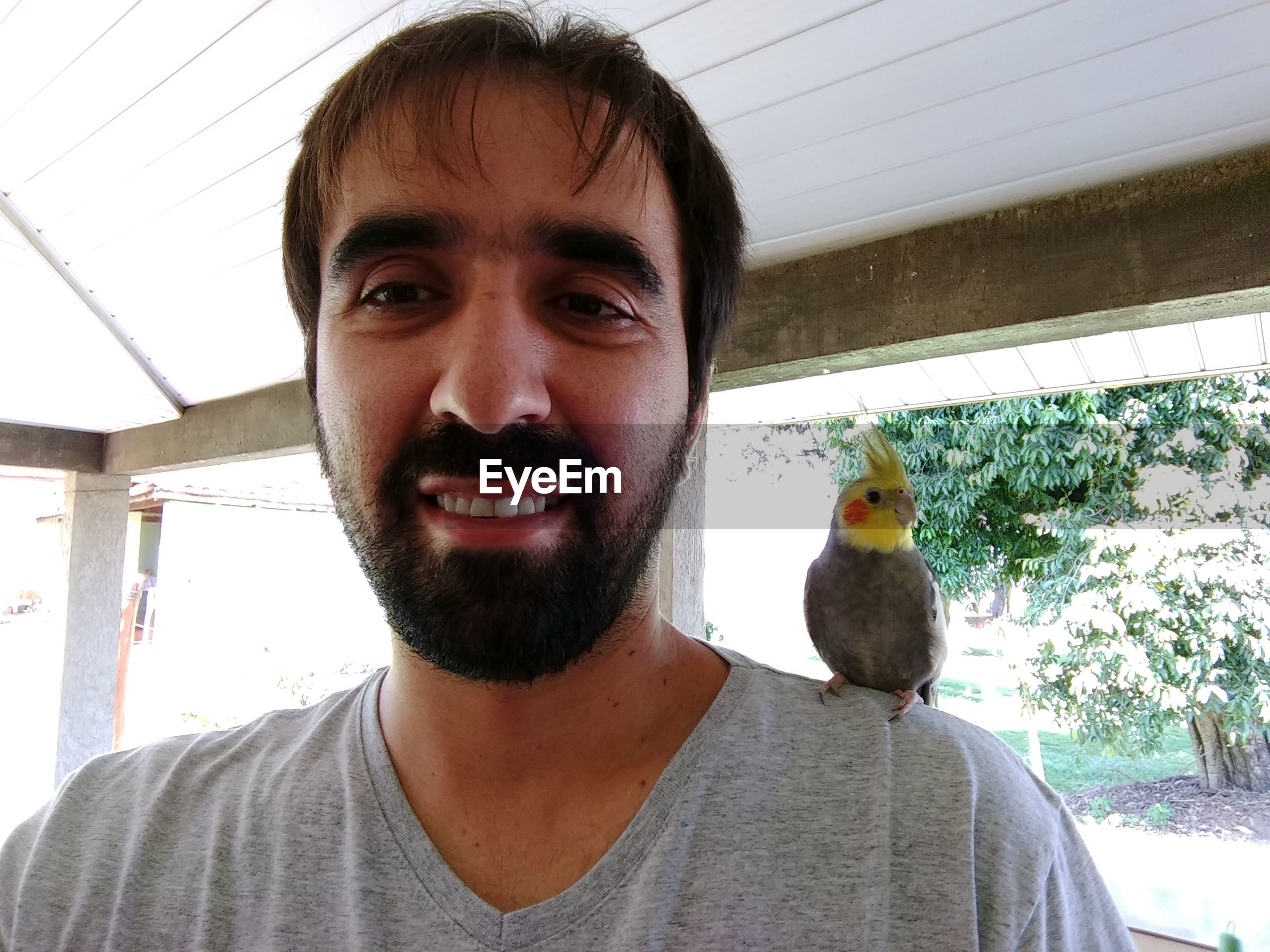 Portrait of smiling man with cockatiel