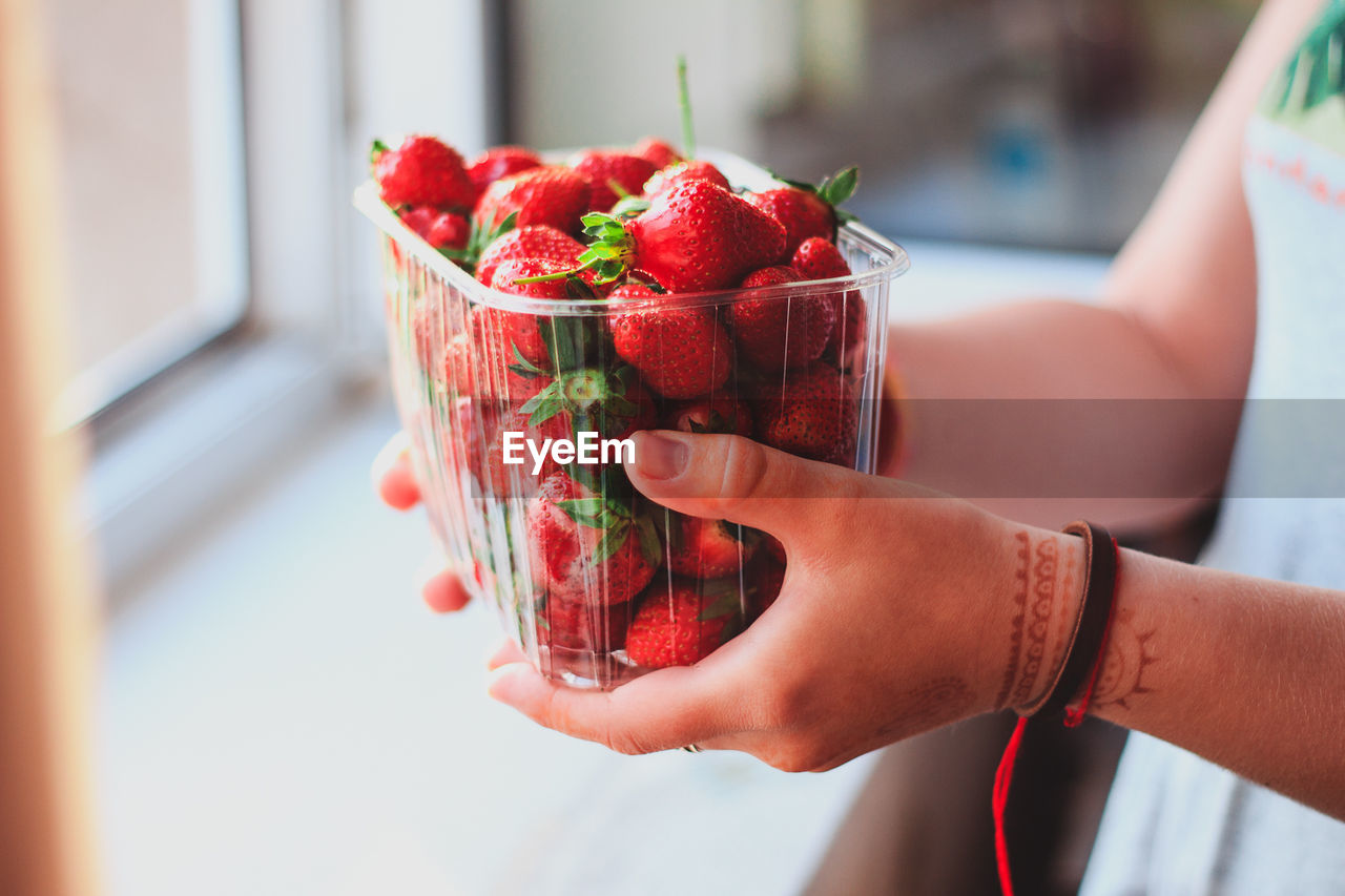 Close-Up Of Hand Holding Strawberry In Container