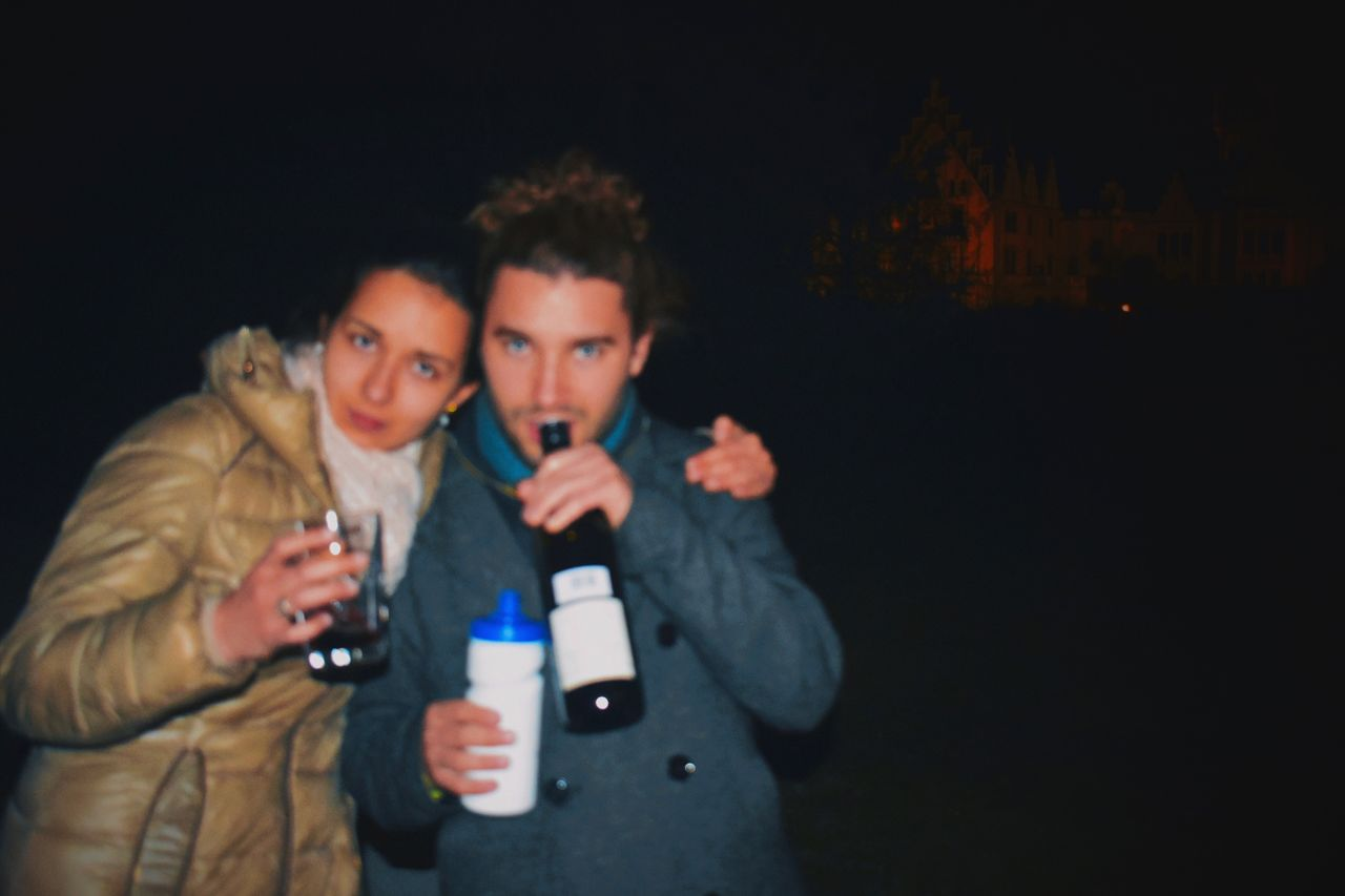 Portrait of young couple having drinks at night