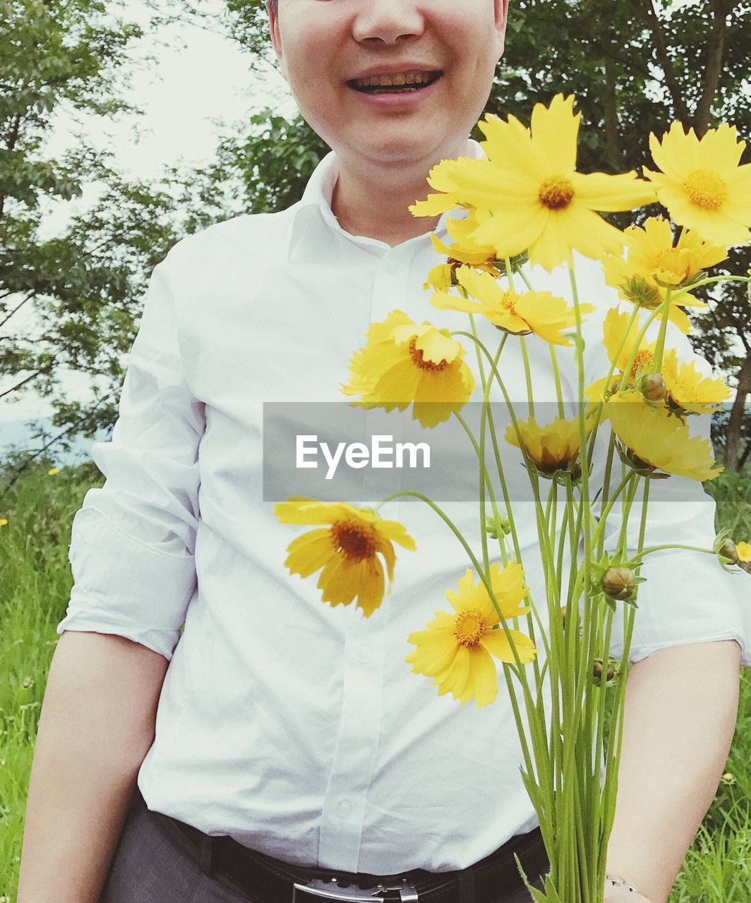 flower, yellow, nature, one person, growth, outdoors, fragility, childhood, beauty in nature, real people, flower head, petal, freshness, front view, day, girls, sunflower, smiling, close-up