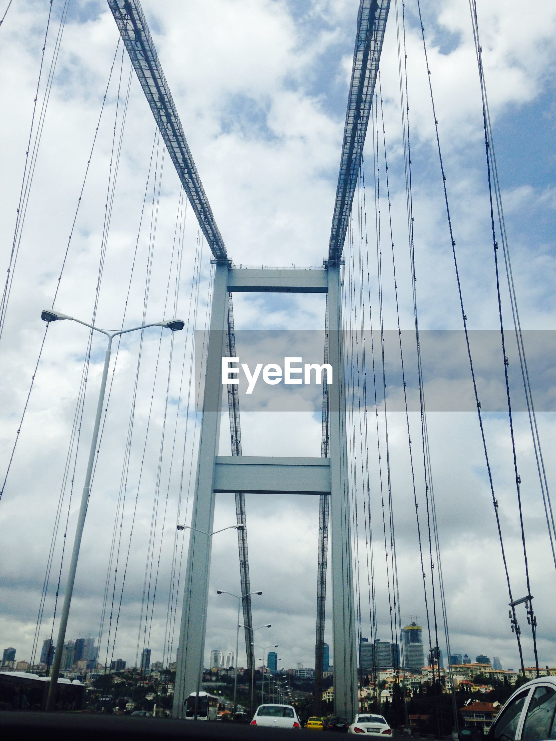 transportation, sky, mode of transport, cloud - sky, connection, low angle view, built structure, car, cloudy, architecture, engineering, bridge - man made structure, land vehicle, travel, cloud, city, suspension bridge, outdoors, day, cable